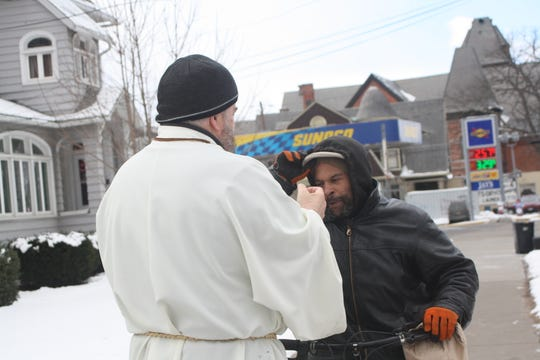 Todd Eames, a deacon at Redeemer Lutheran Church in Binghamton, distributes ashes on Main Street for as part of a Drive-Thru Ashes event for Ash Wednesday.