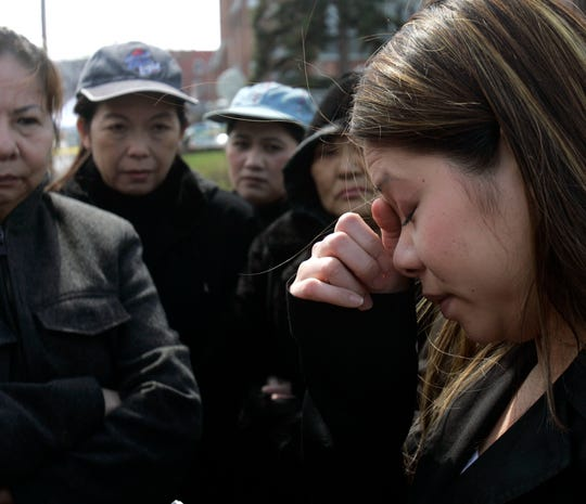 Tina Nguyen, who is related to victims of Friday's shooting at the American Civic Association in Binghamton, talks to reporters outside the community center on Sunday, April 5, 2009.  She is surrounded by family and friends.