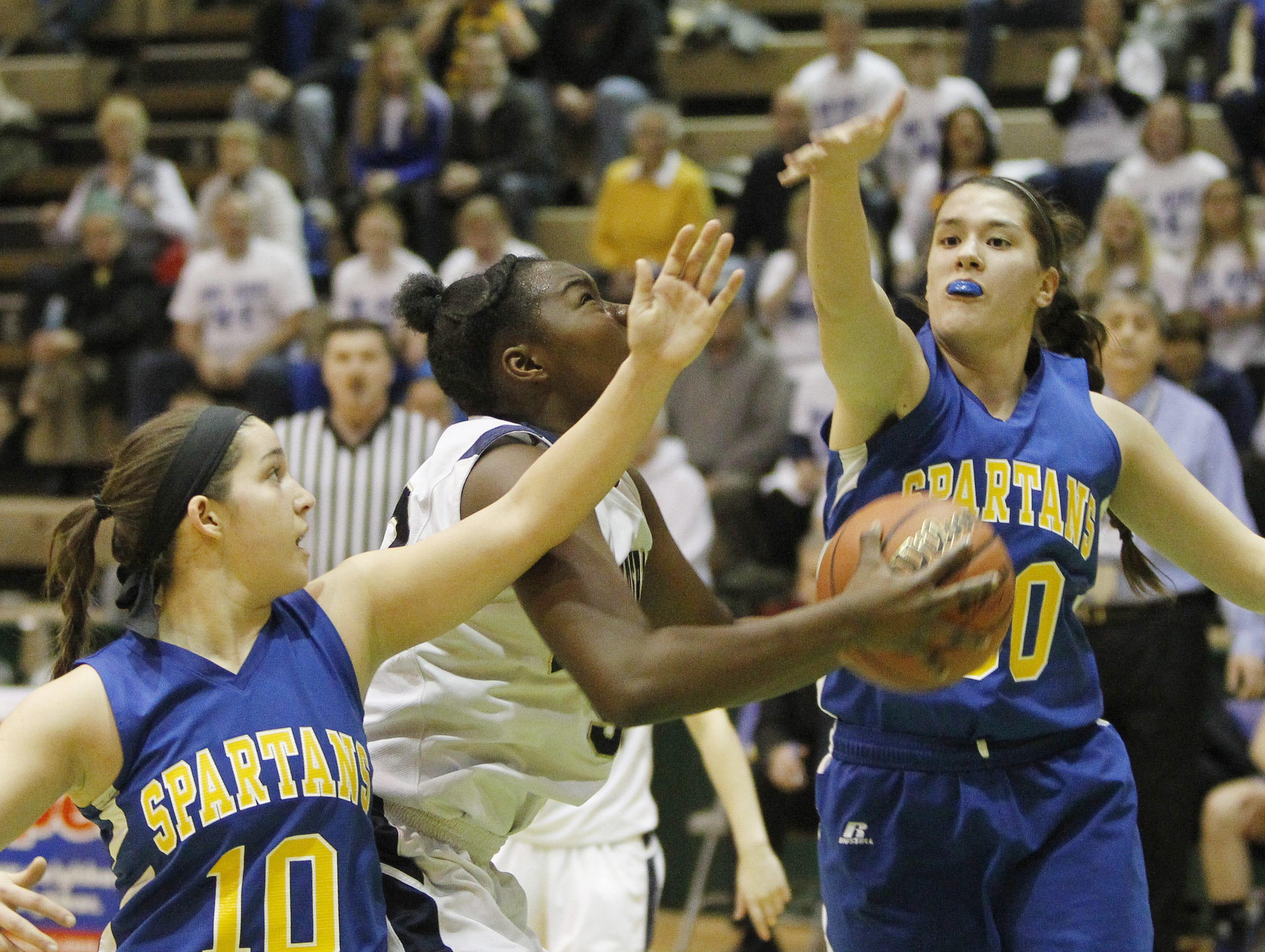 2014: Pittsford Sutherland's Sanita Ebangwese tries to split the Spartans defense of Daniella Dean, left, and Julie Yacovoni in the Class A state semifinals Friday in Troy. Yacovoni scored 11 points and Dean 10 in Maine-Endwell?s 43-39 loss.