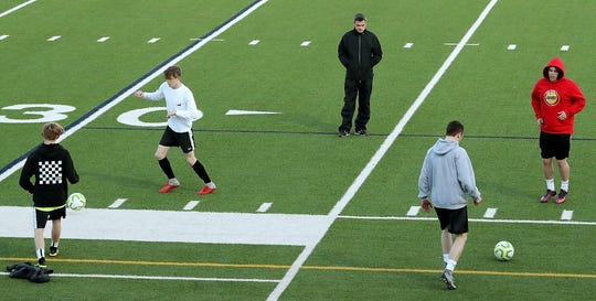 South Kitsap boys soccer coach Cory Vartanian (center) looks on as his team runs through drills during a practice on March 5. The Wolves reached the Class 4A state tournament in 2018.