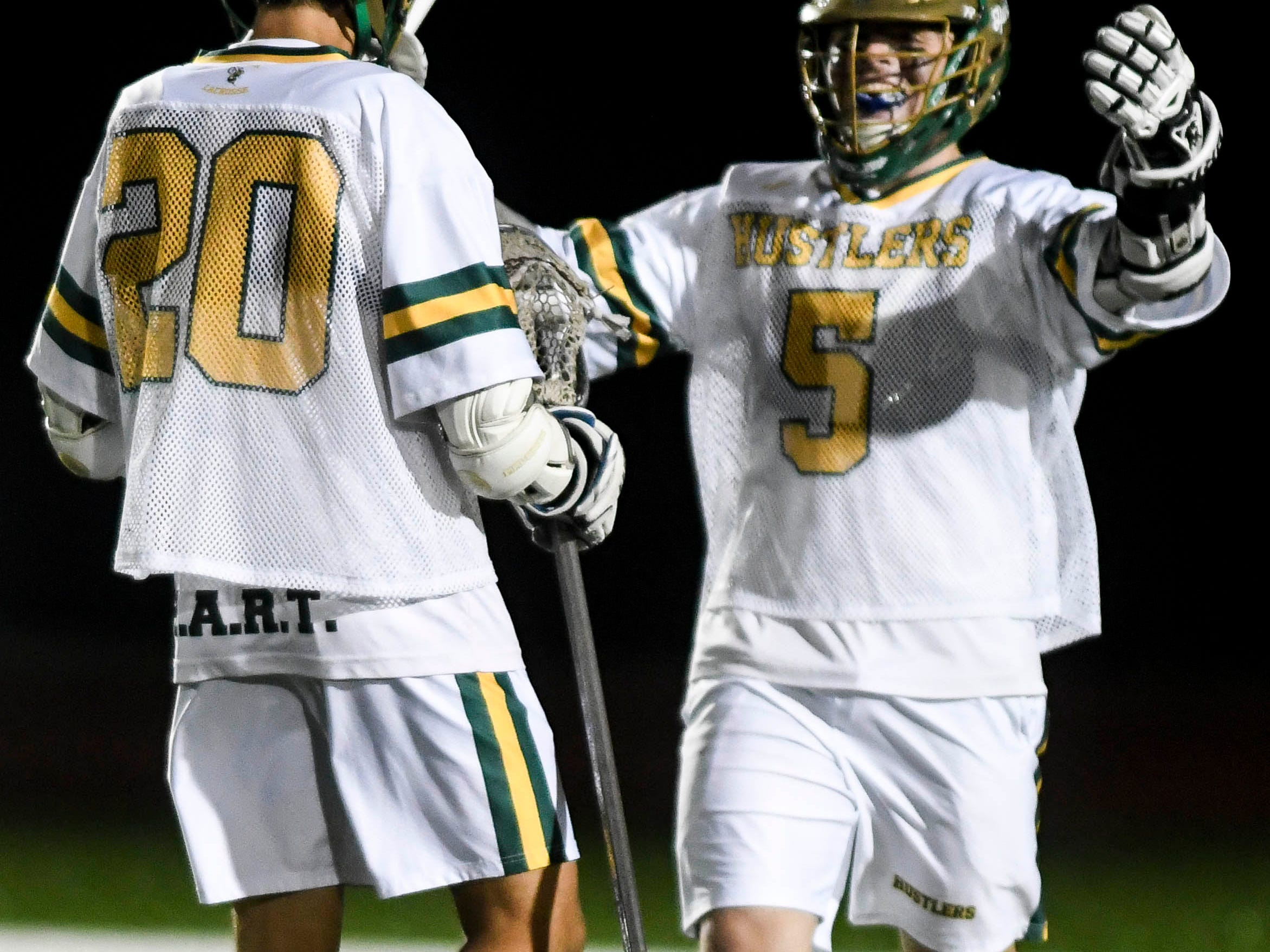 Sam Johnson of Melbourne Central Catholic (5) congratulates teammate Tanner Penn after he scored during Tuesday's game against Academy of the New Church.