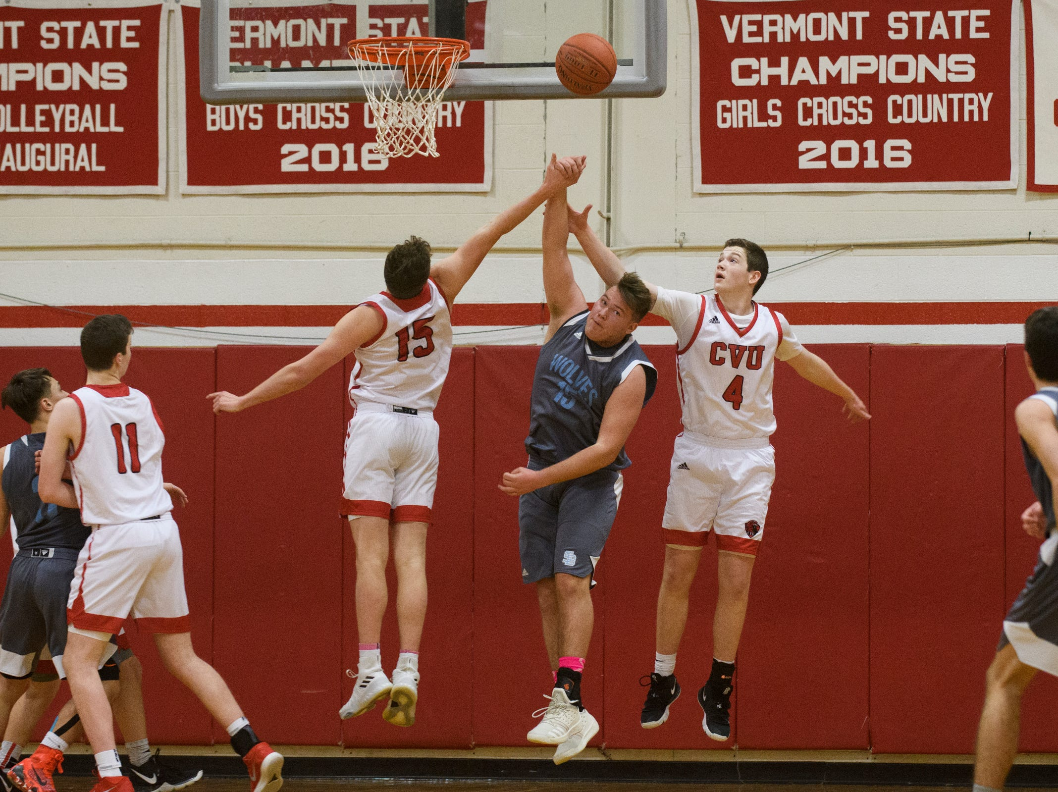 "CVU""s Mason Otley (4) and Bennett Cheer (15) battle for the rebound with South Burlington's Owen McDonough (15) during the boys basketball game between he South Burlington Wolves and the Champlain Valley Union Redhawks at CVU High School on Tuesday night March 5, 2019 in Hinesburg, Vermont."