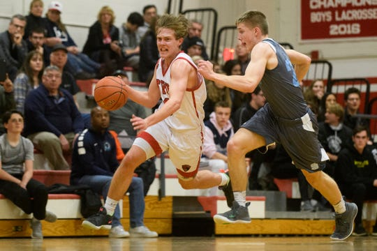 CVU's Ethan Harvey (5) runs past South Burlington's Tyler Gammon (23) with the ball during the boys basketball game between he South Burlington Wolves and the Champlain Valley Union Redhawks at CVU High School on Tuesday night March 5, 2019 in Hinesburg, Vermont.
