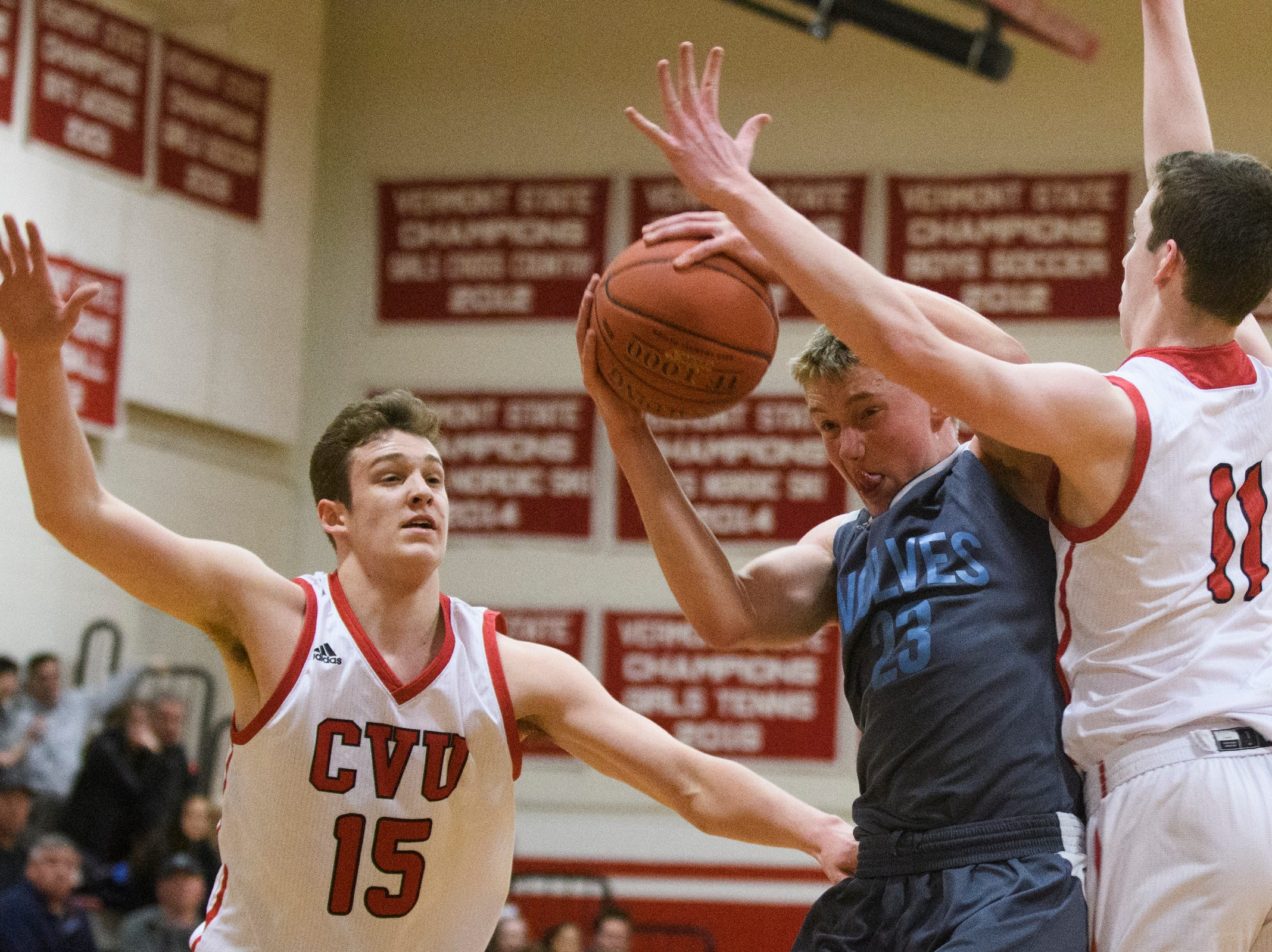 South Burlington's Tyler Gammon (23) battles for the rebound with CVU's Bennett Cheer (15) and Cole Otley (11) during the boys basketball game between he South Burlington Wolves and the Champlain Valley Union Redhawks at CVU High School on Tuesday night March 5, 2019 in Hinesburg, Vermont.