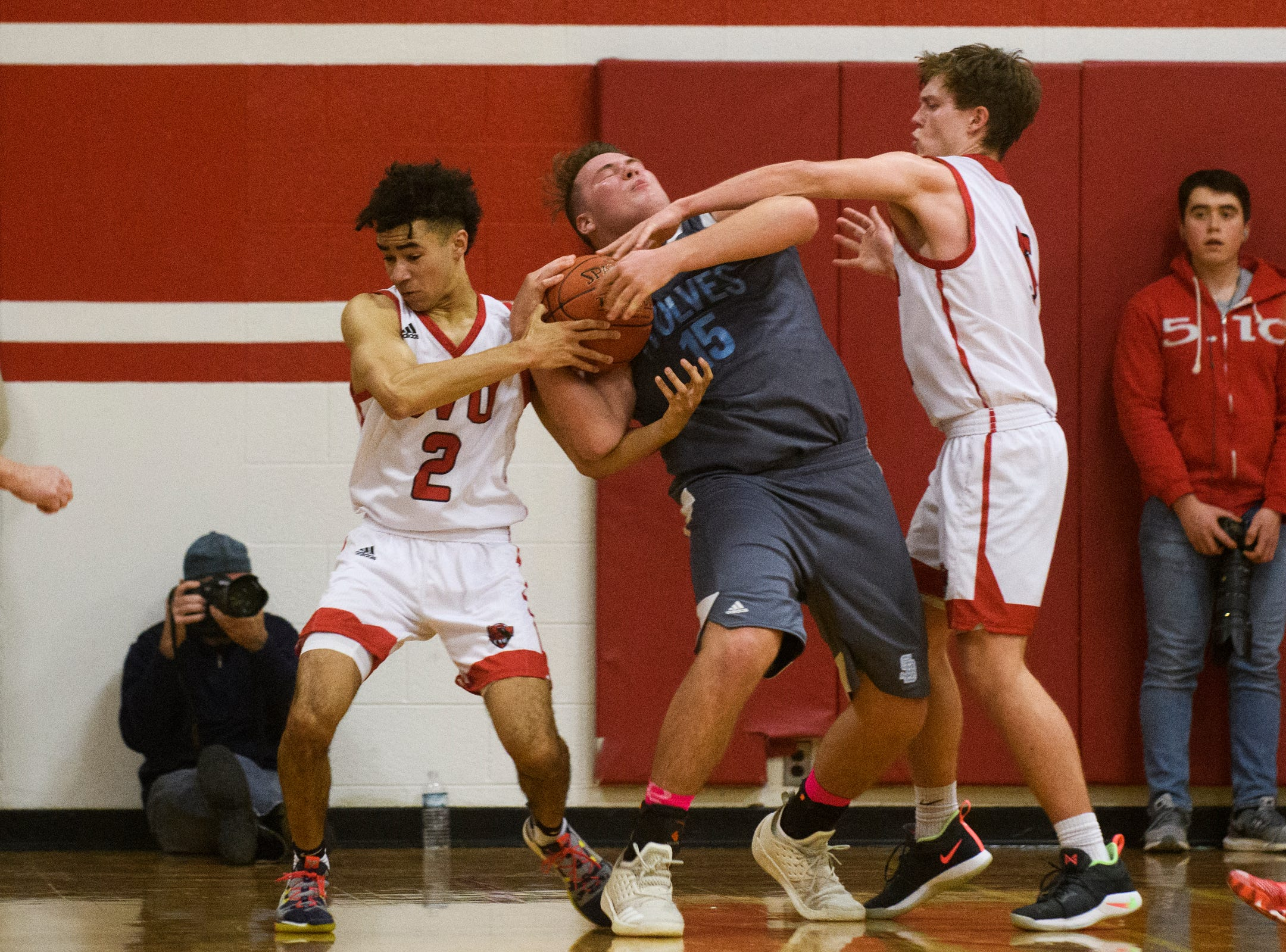 South Burlington's Owen MacDonough (15) battles for the ball with CVU's Noah Martin (2) and Ethan Harvey (5) during the boys basketball game between he South Burlington Wolves and the Champlain Valley Union Redhawks at CVU High School on Tuesday night March 5, 2019 in Hinesburg, Vermont.