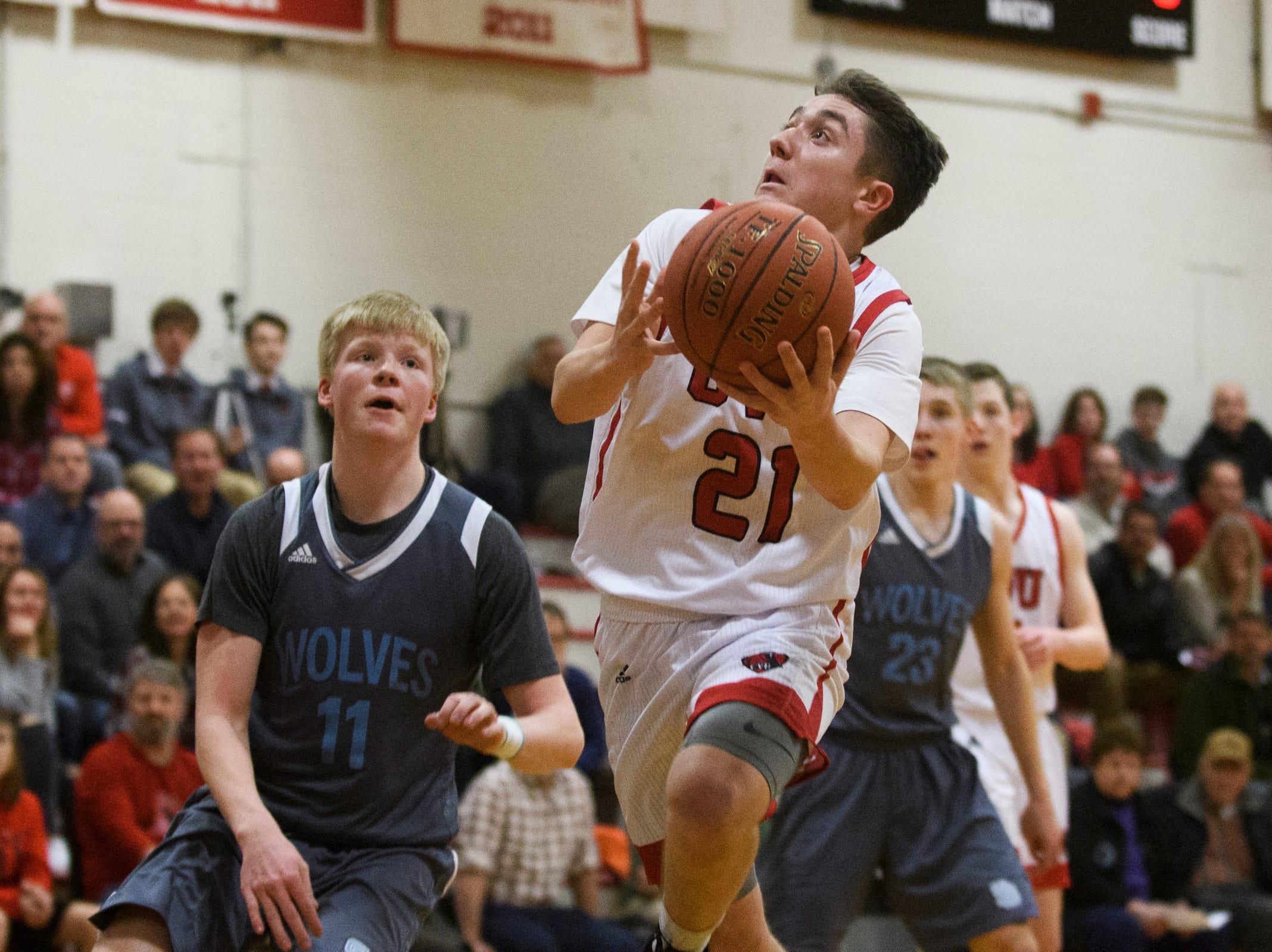 CVU's Nikos Carroll (21) leaps for a lay up during the boys basketball game between he South Burlington Wolves and the Champlain Valley Union Redhawks at CVU High School on Tuesday night March 5, 2019 in Hinesburg, Vermont.