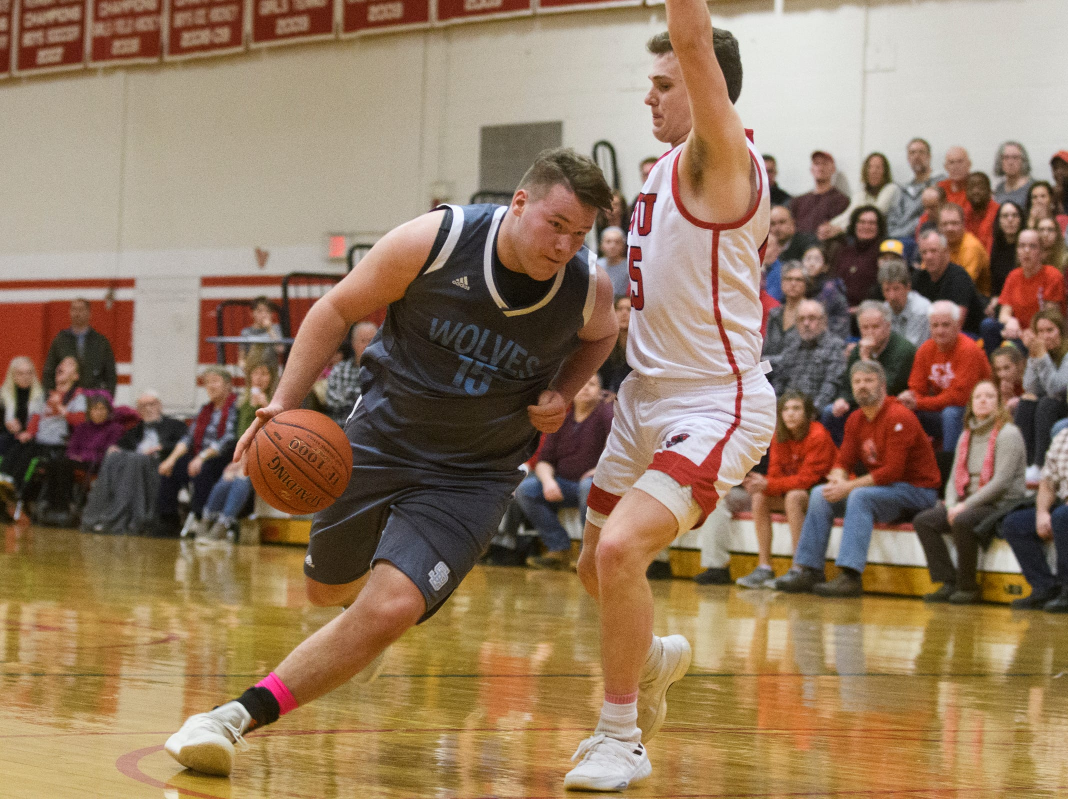 South Burlington's Owen McDonough (15) drives to the hoop past CVU's Bennett Cheer (15) during the boys basketball game between he South Burlington Wolves and the Champlain Valley Union Redhawks at CVU High School on Tuesday night March 5, 2019 in Hinesburg, Vermont.