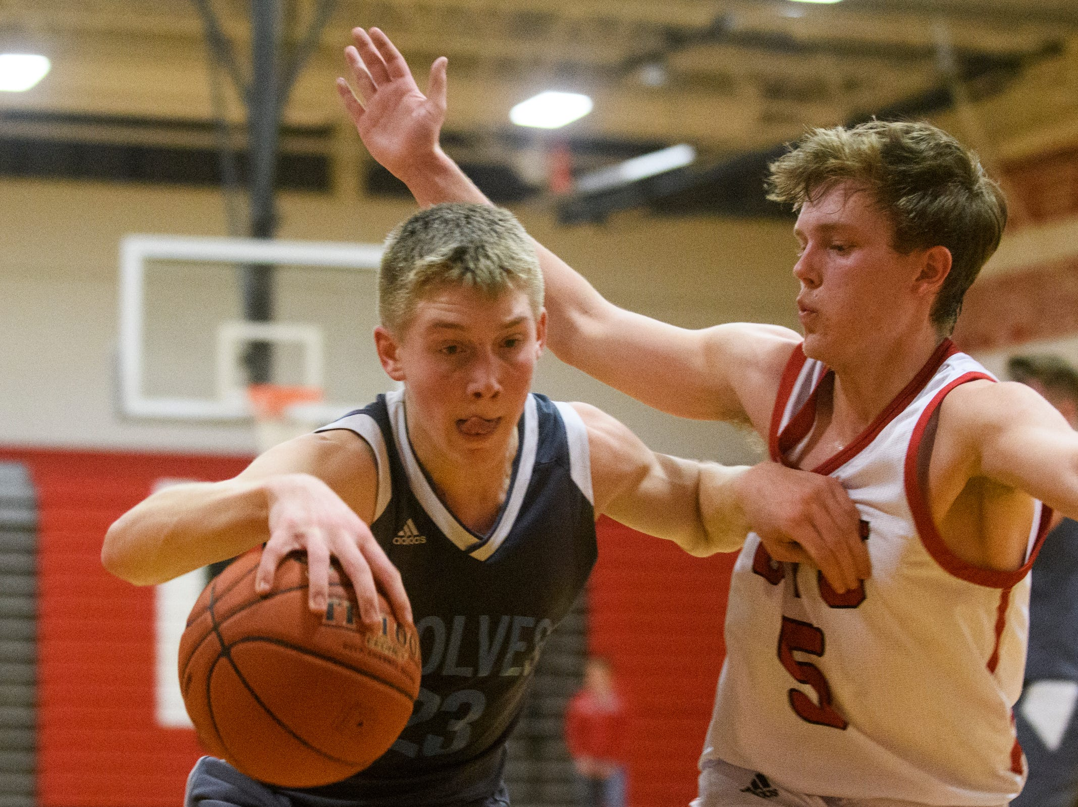 CVU's Ethan Harvey (5) guards South Burlington's Tyler Gammon (23) during the boys basketball game between he South Burlington Wolves and the Champlain Valley Union Redhawks at CVU High School on Tuesday night March 5, 2019 in Hinesburg, Vermont.