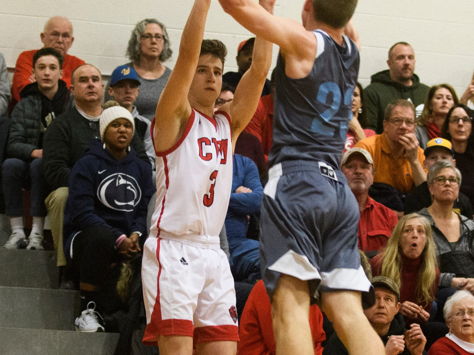 CVU's Jason West (3) shoots the ball over South Burlington's Tyler Gammon (23) during the boys basketball game between he South Burlington Wolves and the Champlain Valley Union Redhawks at CVU High School on Tuesday night March 5, 2019 in Hinesburg, Vermont.