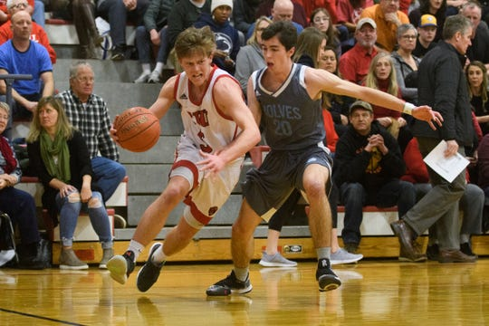 CVU's Ethan Harvey (5) drives to the hoop past South Burlington's Brendan Bridge (20) during the boys basketball game between he South Burlington Wolves and the Champlain Valley Union Redhawks at CVU High School on Tuesday night March 5, 2019 in Hinesburg, Vermont.