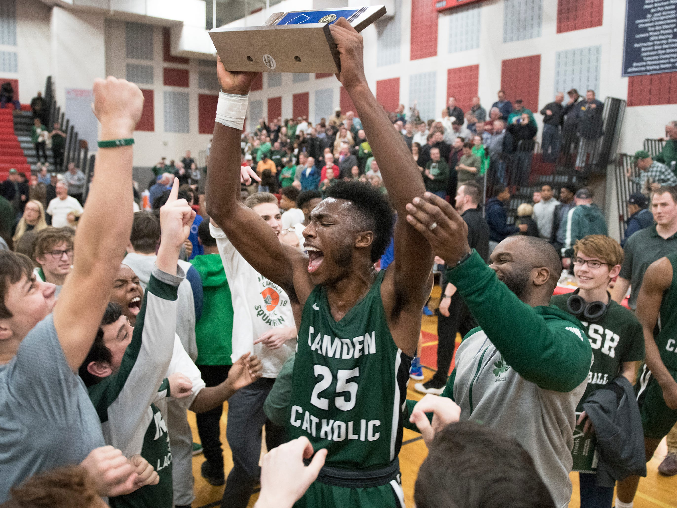 Camden Catholic's Babatunde Ajike hoists the trophy after Camden Catholic defeated Paul VI, 40-34, in the Non-Public A South boys basketball final played at Jackson Liberty High School on Tuesday, March 5, 2019.