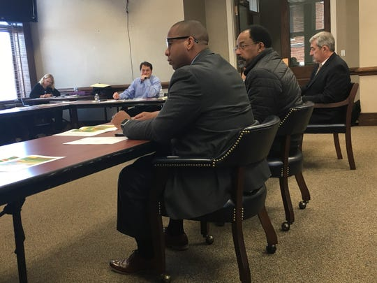 Clarksville-Montgomery County Schools Director Millard House, in foreground, seated beside School Board member Jimmie Garland, weigh the options of finding a new site for a middle school.