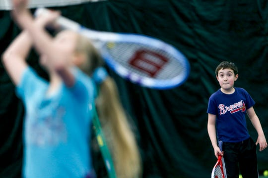 Aaron Harsson, 8, watches as Grace Brosslaine, 10, returns a hit while practicing with their parents at Governor's Indoor Tennis Center in Clarksville, Tenn., Tuesday, March 5, 2019.