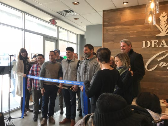 Metuchen mayor Jonathan Busch (center left) and Dean's owner and founder Dean Nelson (center right, wearing a Dean's sweatshirt) were on hand for the ribbon-cutting ceremony at Dean's Café in Metuchen on February 2nd