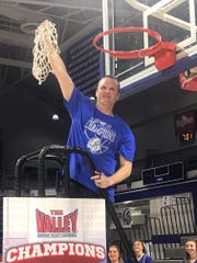 Drake coach Darian DeVries finishes cutting down the nets during a ceremony at the Knapp Center Tuesday night.