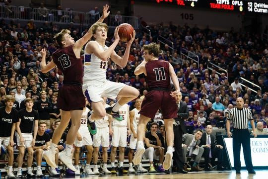 Waukee's Tucker DeVries (12) shoots around Dowling Catholic's Jack Lyman (13) during their boys 4A state basketball tournament game on Wednesday, March 6, 2019, in Des Moines. Waukee would go on to defeat Dowling Catholic 48-35.