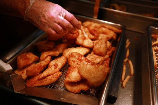 A church work plates fried fish during a Friday fish fry at First United Methodist Church in Royal Oak.