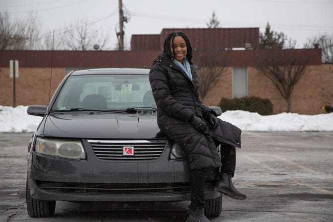 Amanda Hill, 27, poses next to her 2005 Saturn Ion she bought last year in order to avoid car payments. She paid $500 for that car but she's dealing with $90,000 in student loan debt.