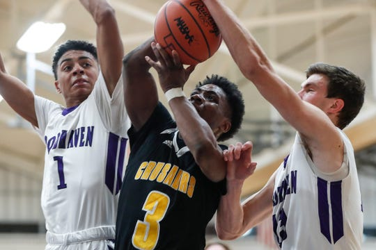 King's Jordan Whitford (3) battles for a rebound with Woodhaven's Marcus Brown (1) and Colin Czajkowski (13) during the second half of regional semifinal at Lincoln Park High School in Lincoln Park, Tuesday, March 5, 2019.