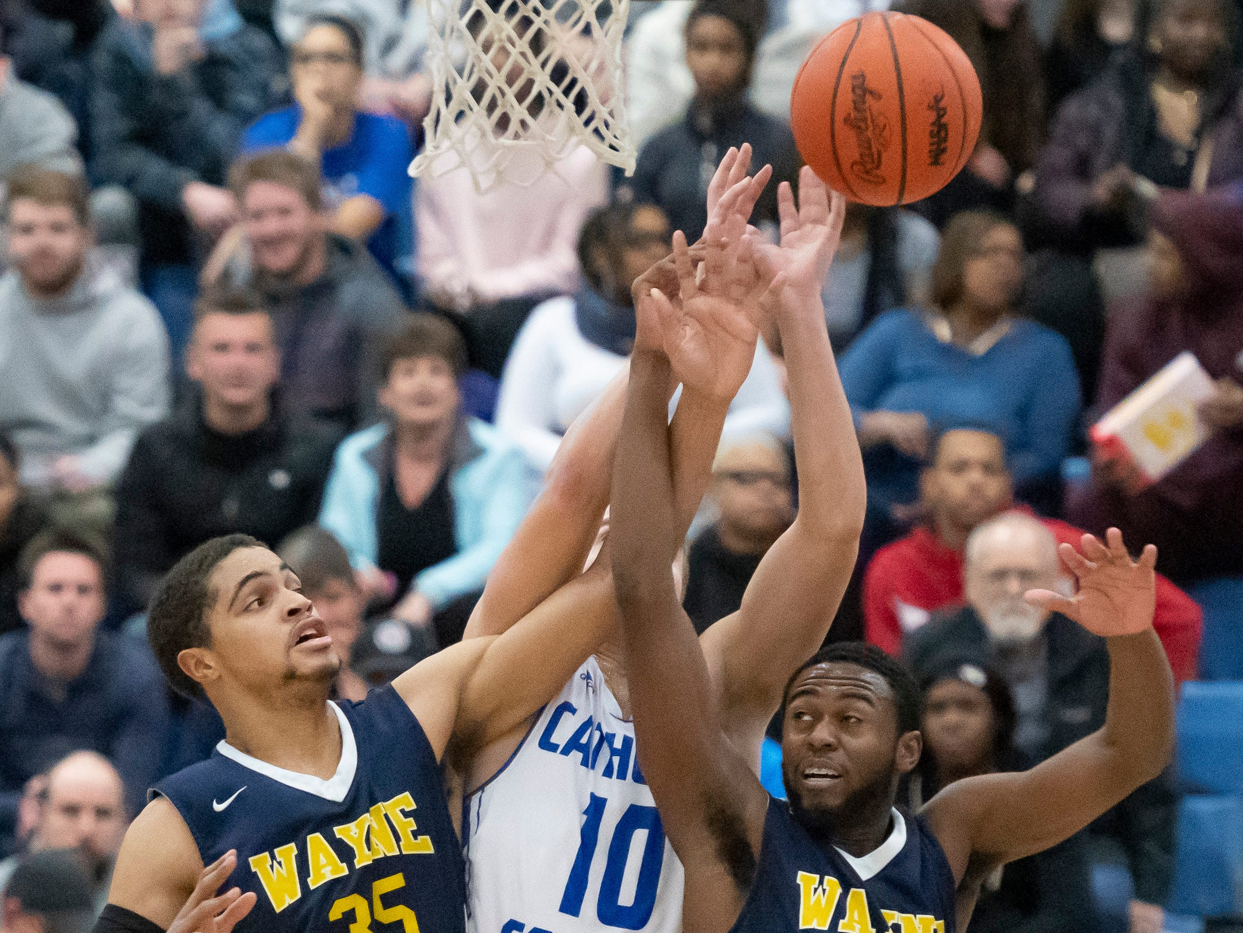 Wayne Memorial forward Dreyon O'Neal, left, and Chayce Leslie try to grab a rebound away from Detroit Catholic Central's Mike Harding in the first half.