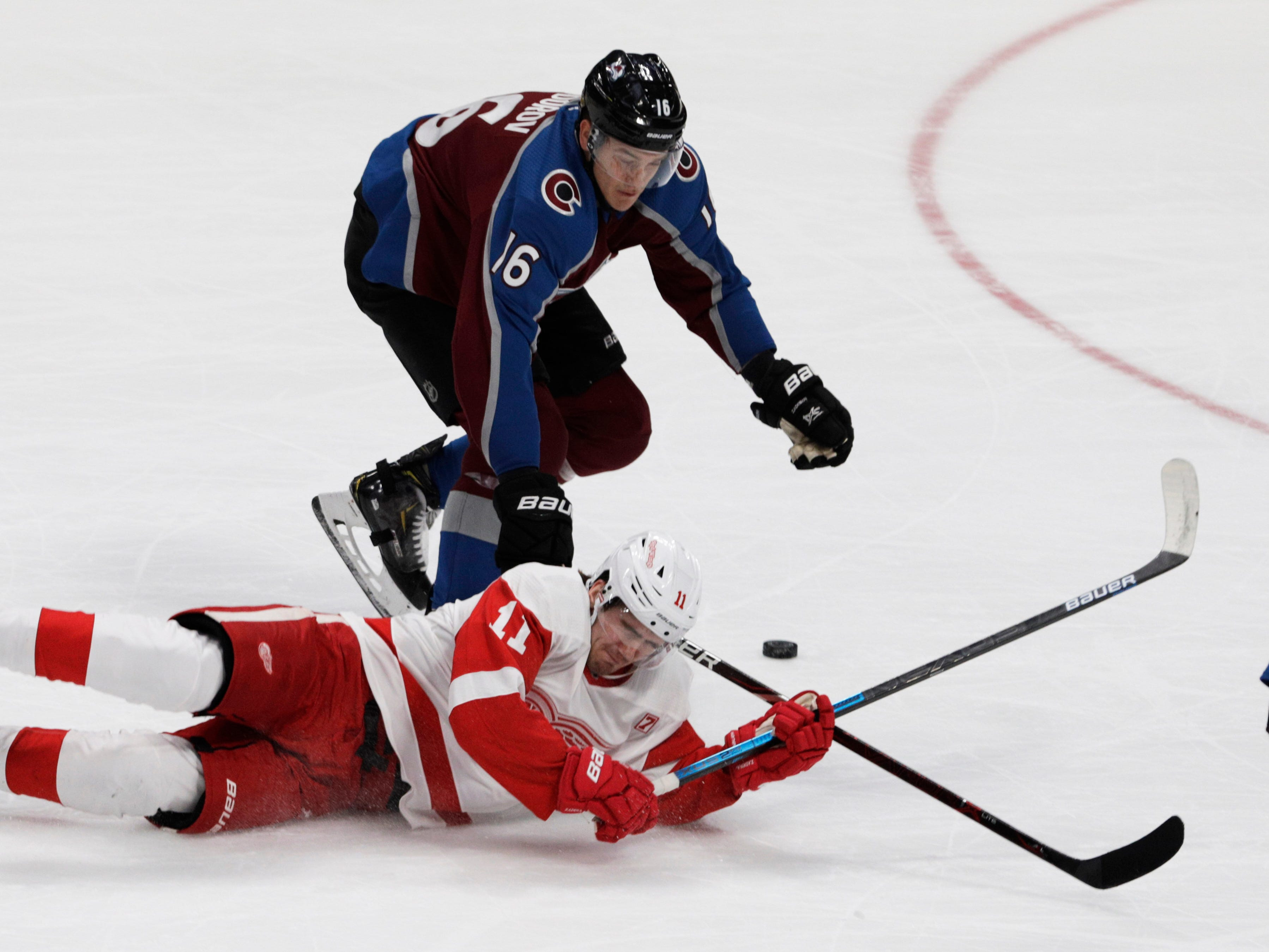 Detroit Red Wings right wing Filip Zadina (11) falls to the ice as Colorado Avalanche defenseman Nikita Zadorov (16) defends during the first period of an NHL hockey game in Denver, Tuesday, March 5, 2019