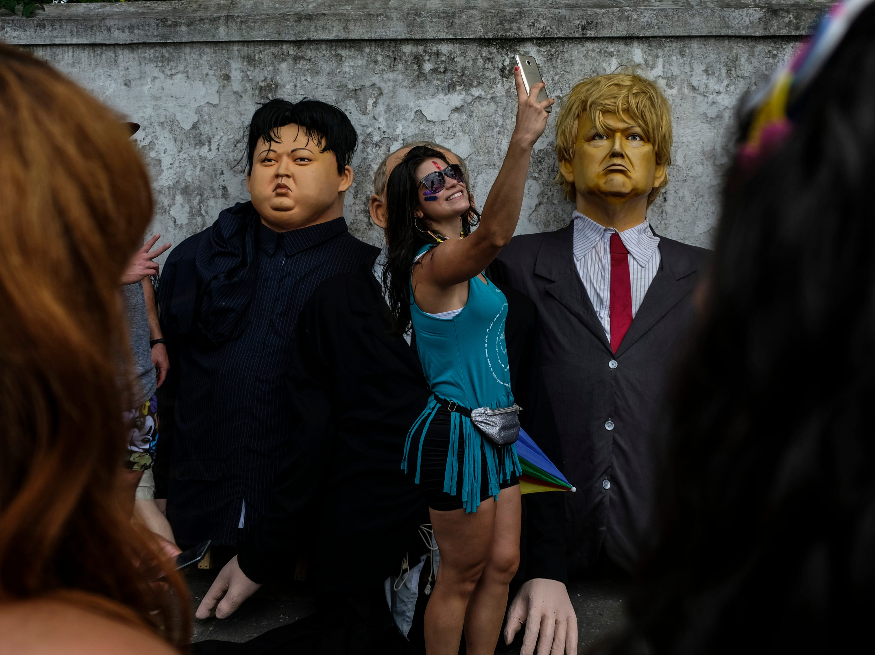 A woman takes a selfie next to giant dolls depicting U.S. President Donald Trump, right, and North Korean leader Kim Jong-un during carnival celebrations in Olinda, Pernambuco state, Brazil, Monday, March 4, 2019.