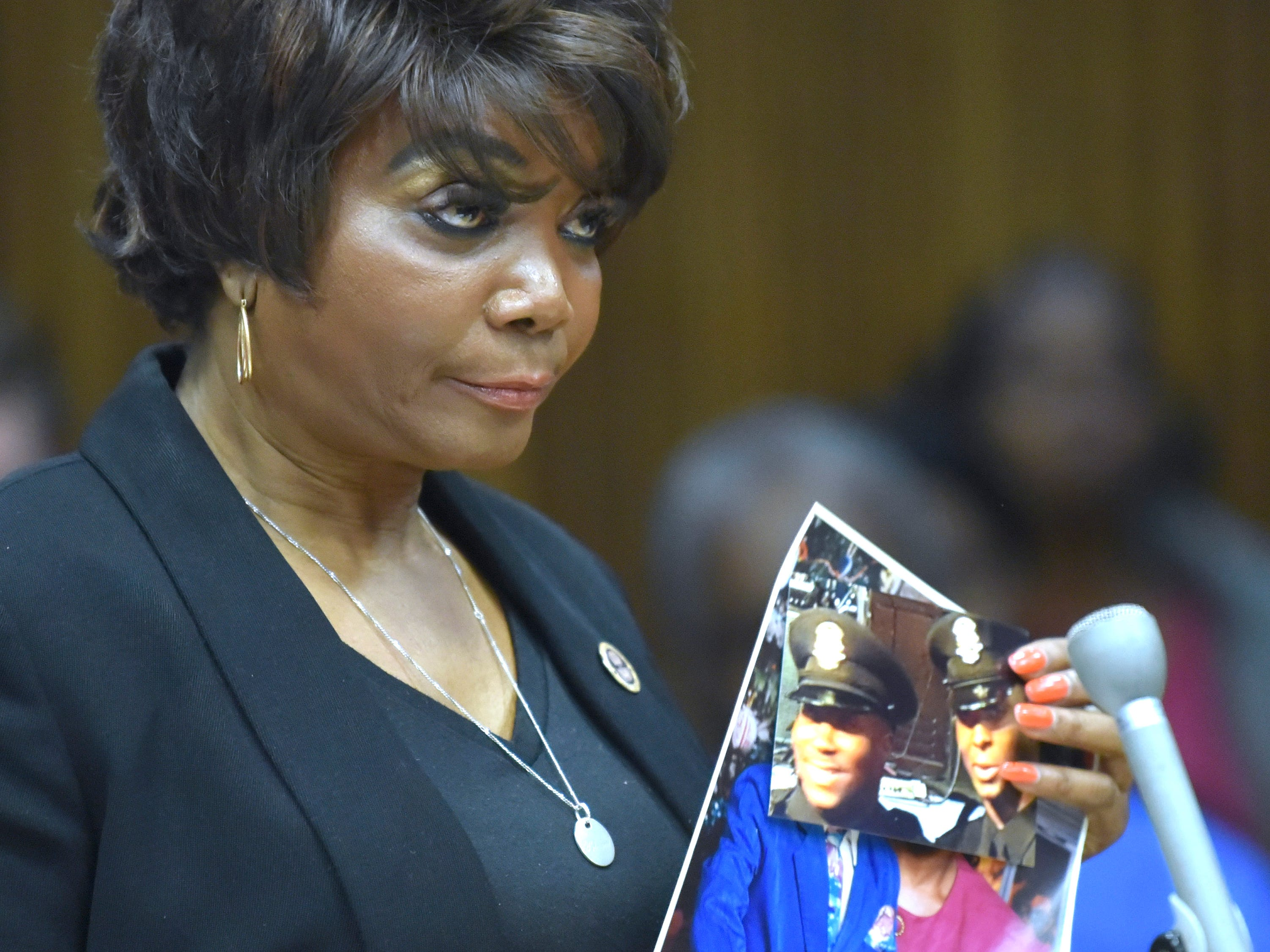 Glenn Doss Jr's grandmother Beretha Bradley holds up a portrait of her son, Detroit Police Officer Glenn Doss Sr, left, and his slain Detroit Police Officer son, right, during her victim's impact statement.