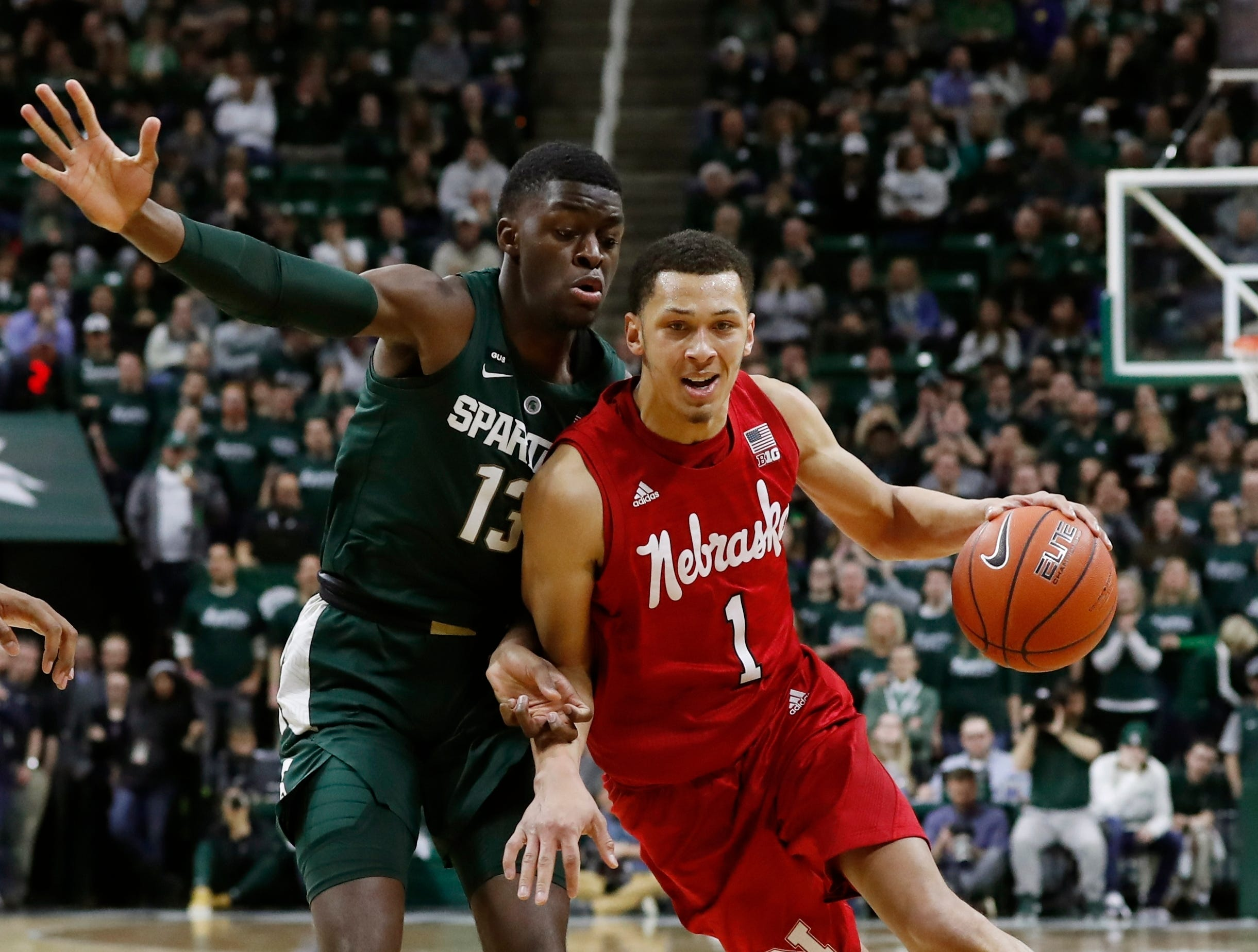 Nebraska guard Amir Harris (1) drives on Michigan State forward Gabe Brown (13) during the first half of an NCAA college basketball game.
