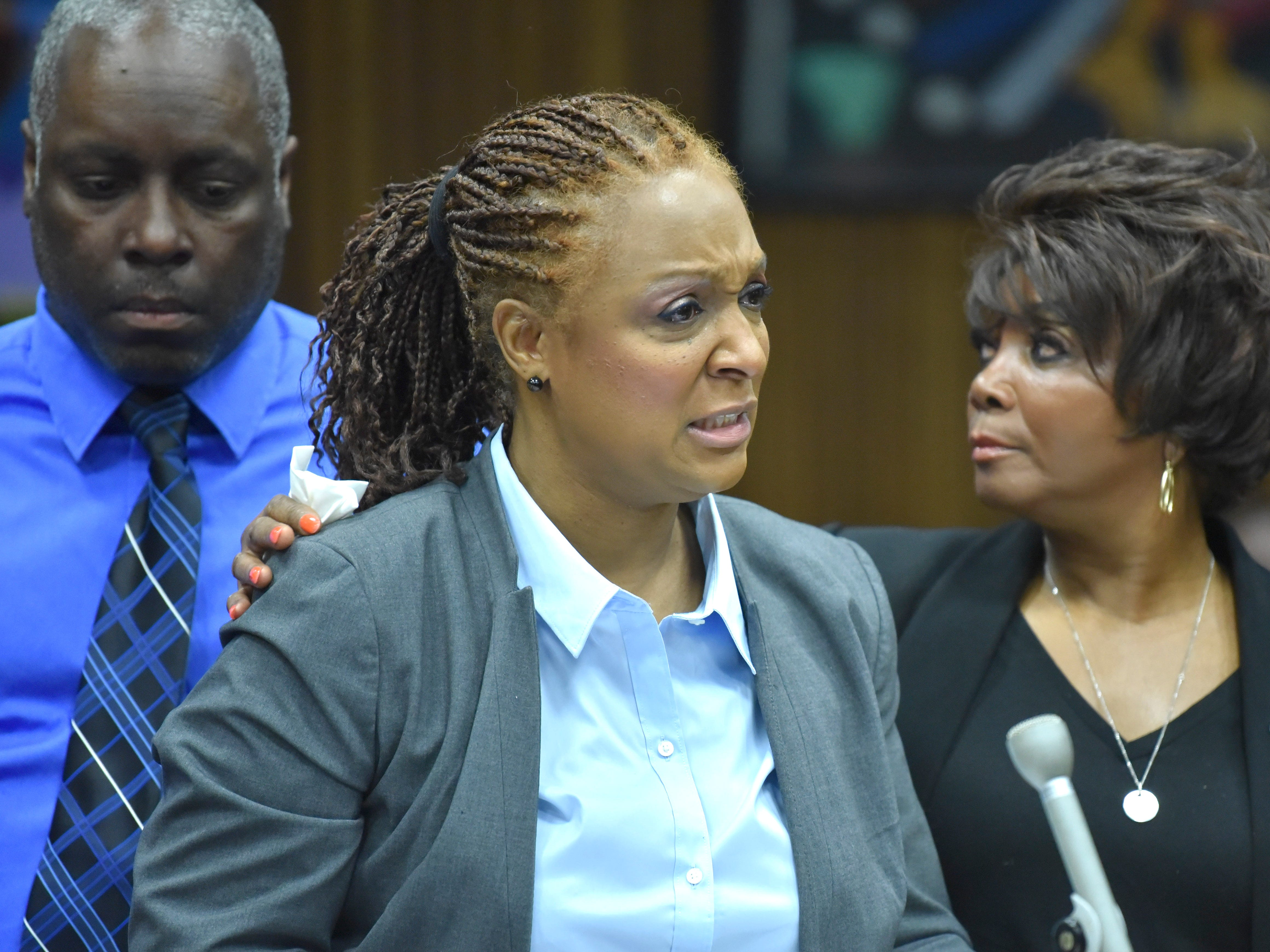 Nikole Flowers, center, mother of Glenn Doss Jr., cries while giving her victim's impact statement as she is comforted by her husband, Ronald Flowers, left, and Doss Jr.'s grandmother, Beretha Bradley, right.