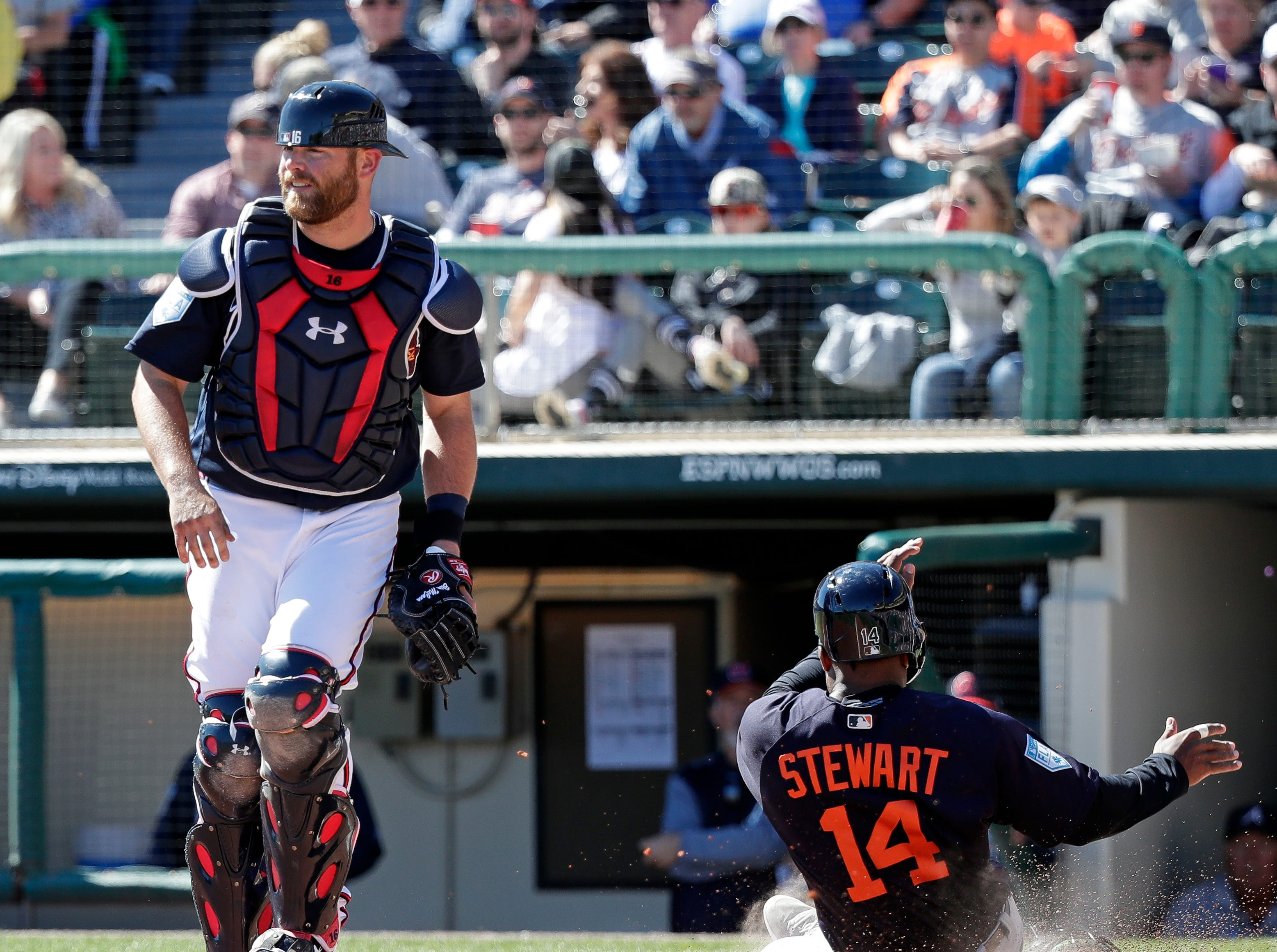 Detroit Tigers' Christin Stewart (14) scores on a base hit by Dustin Peterson in the fourth inning as Atlanta Braves catcher Brian McCann, left, waits for the throw in a spring baseball exhibition game, Wednesday, March 6, 2019, in Kissimmee, Fla