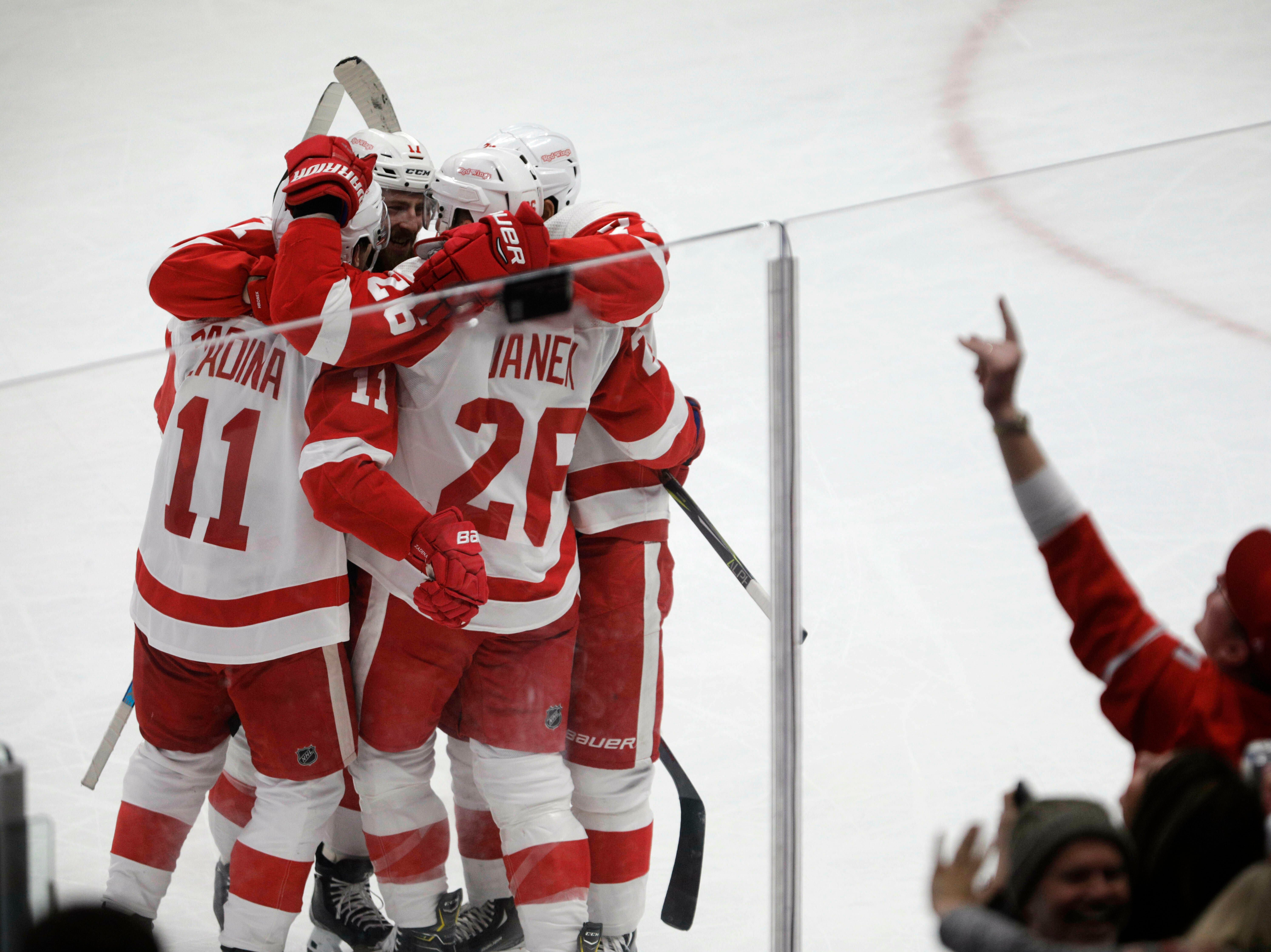 Teammates mob Detroit Red Wings right wing Filip Zadina (11) after his goal against the Colorado Avalanche during the third period of an NHL hockey game in Denver, Tuesday, March 5, 2019. Colorado won 4-3 in overtime. (AP Photo/Joe Mahoney)