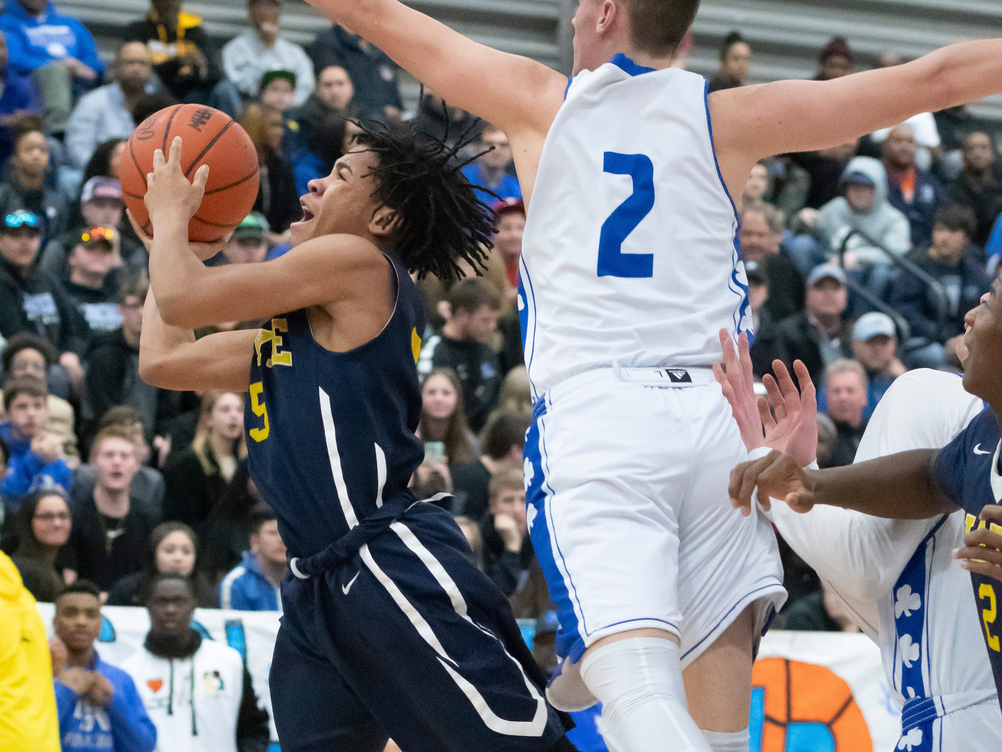 Wayne Memorial guard Kenneth Bowie, left, is defended by Detroit Catholic Central's Brendan Downs in the first half.