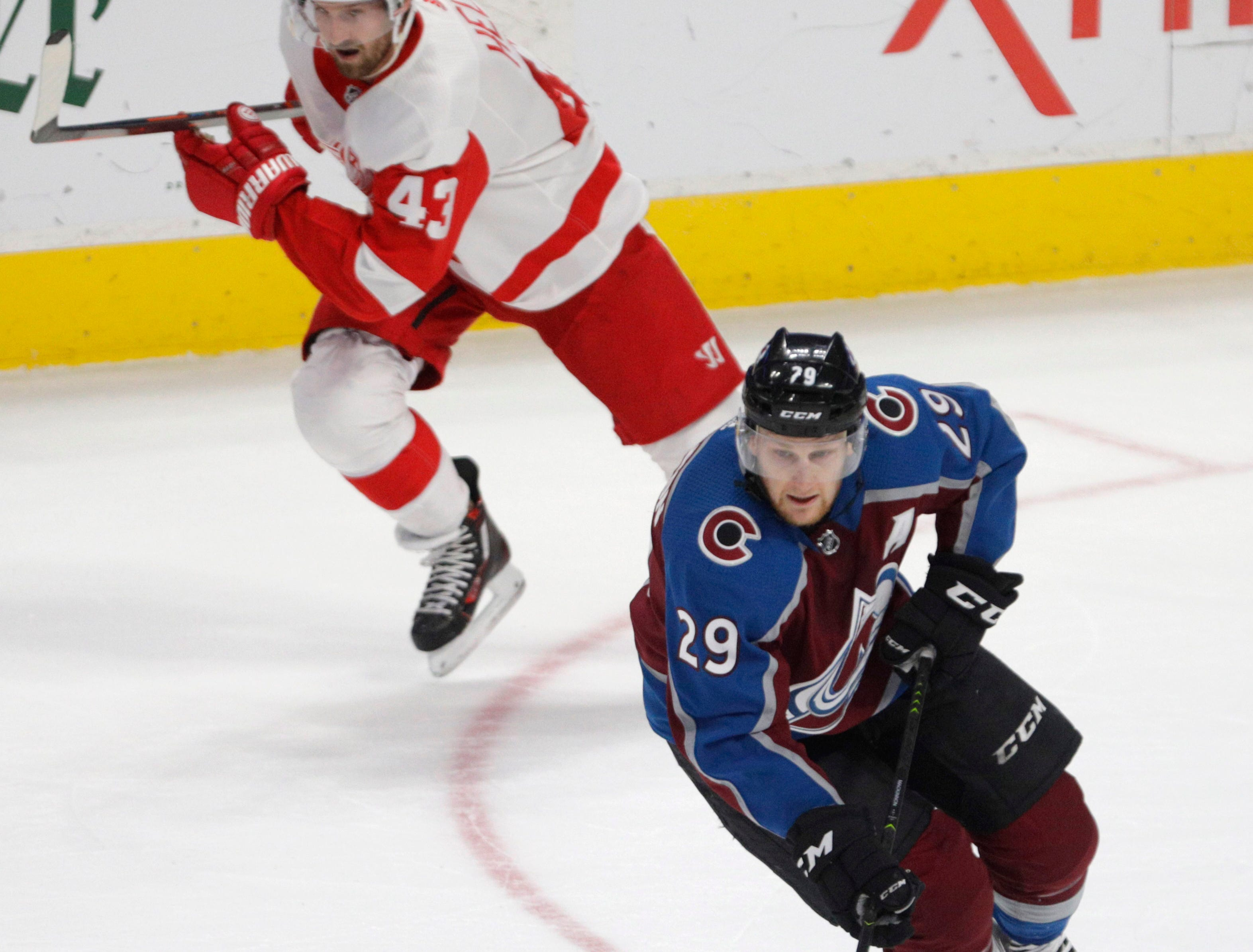 Colorado Avalanche center Nathan MacKinnon (29) skates with the puck as Detroit Red Wings left wing Darren Helm (43) pursues during the third period.