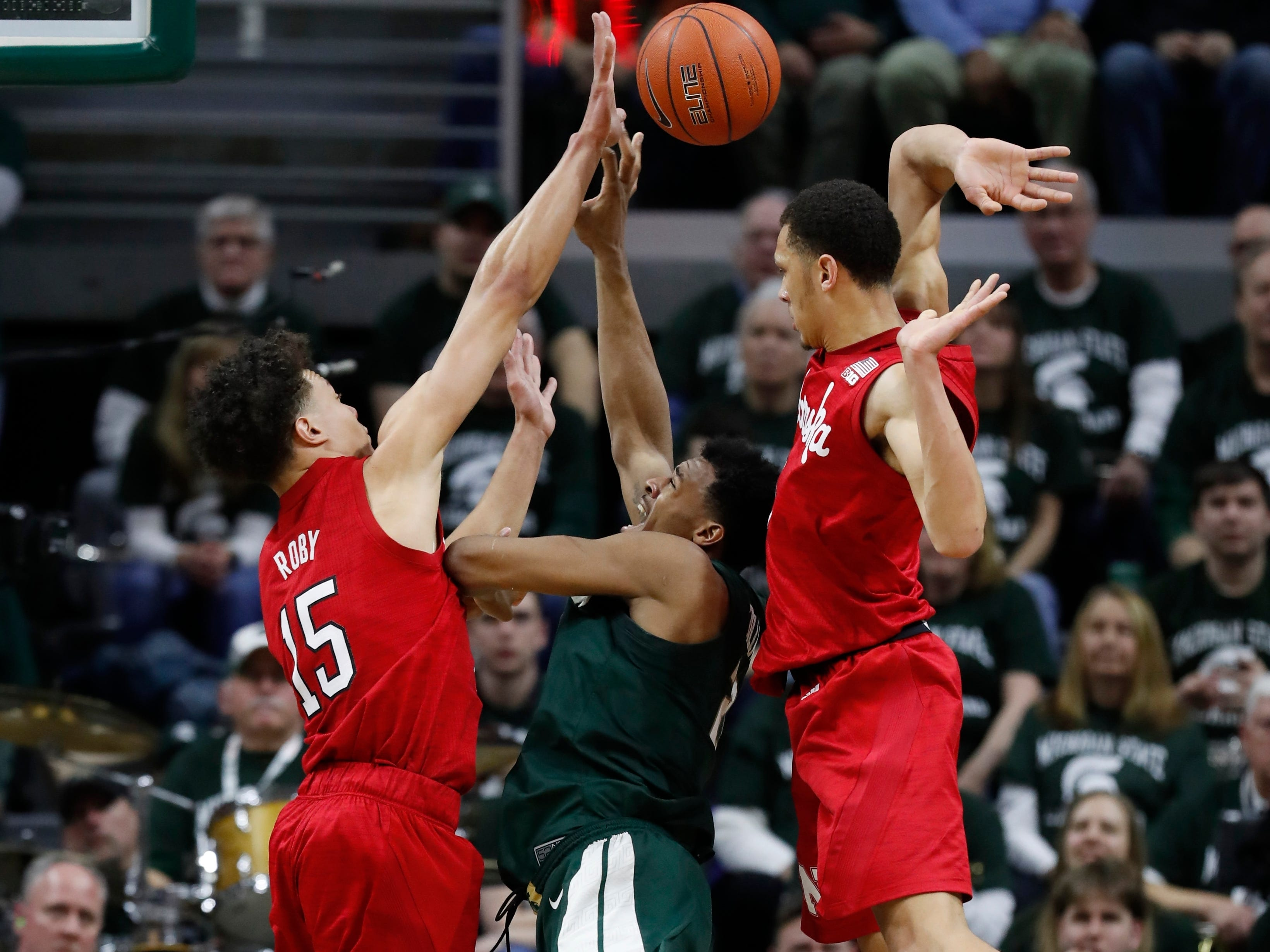 Michigan State forward Xavier Tillman, center, attempts a shot as Nebraska defenders Isaiah Roby, left, and Amir Harris, right, converge on him during the first half of an NCAA college basketball game, Tuesday, March 5, 2019.
