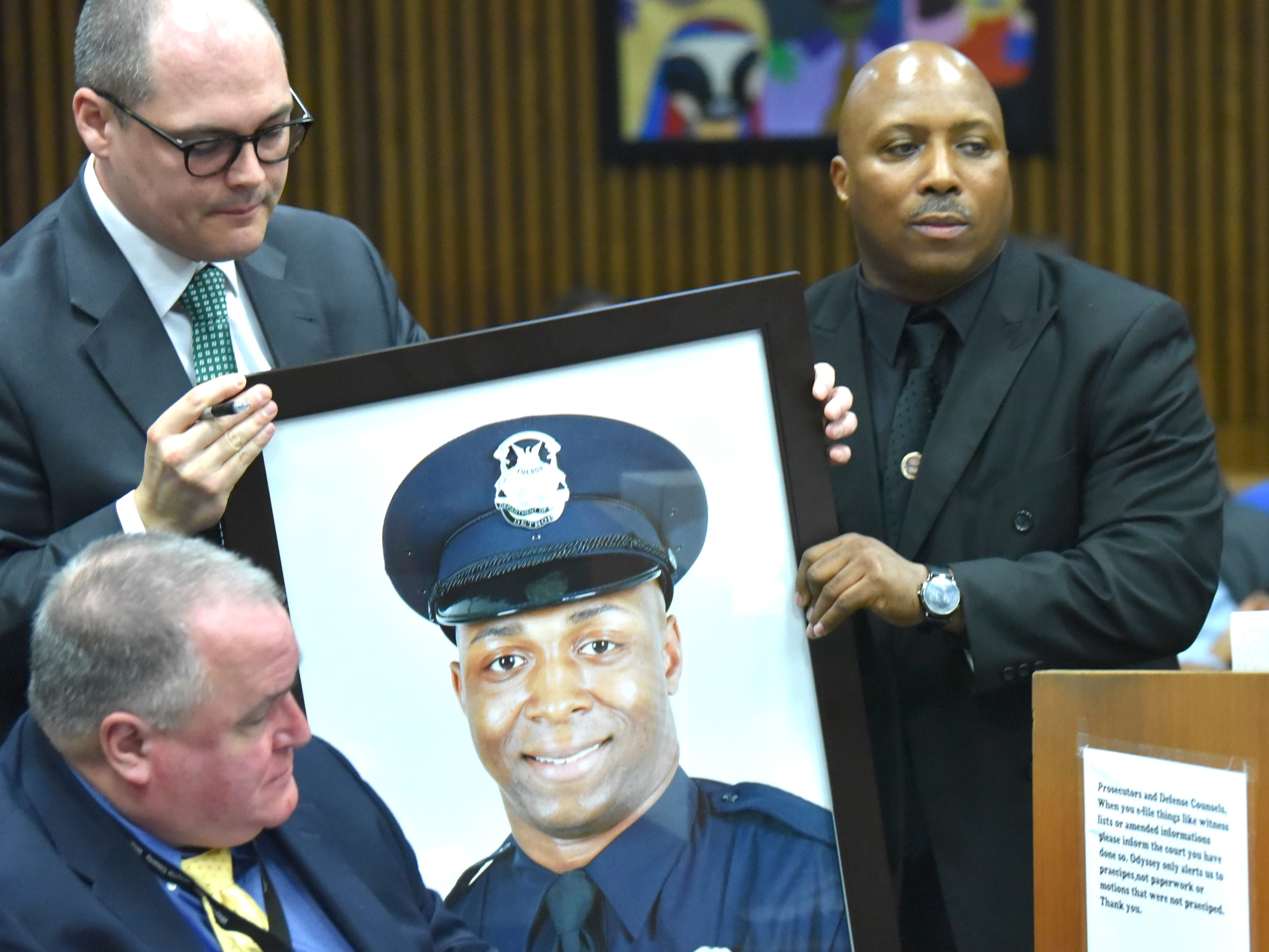 Detroit Police Officer Glenn Doss Sr., right, hands a portrait of his murdered DPD officer son, Glenn Doss Jr., to assistant prosecutor Matthew Penney, left, as he prepares to make his victim's impact statement.