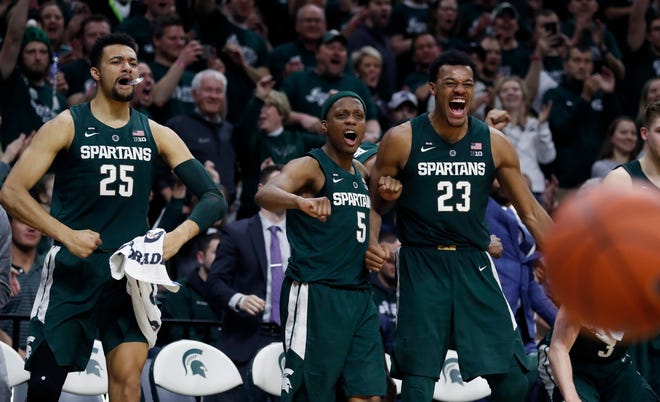 From left, Michigan State forward Kenny Goins (25), guard Cassius Winston (5), and forward Xavier Tillman (23) react after a basket by Brock Washington during the second half Tuesday night.