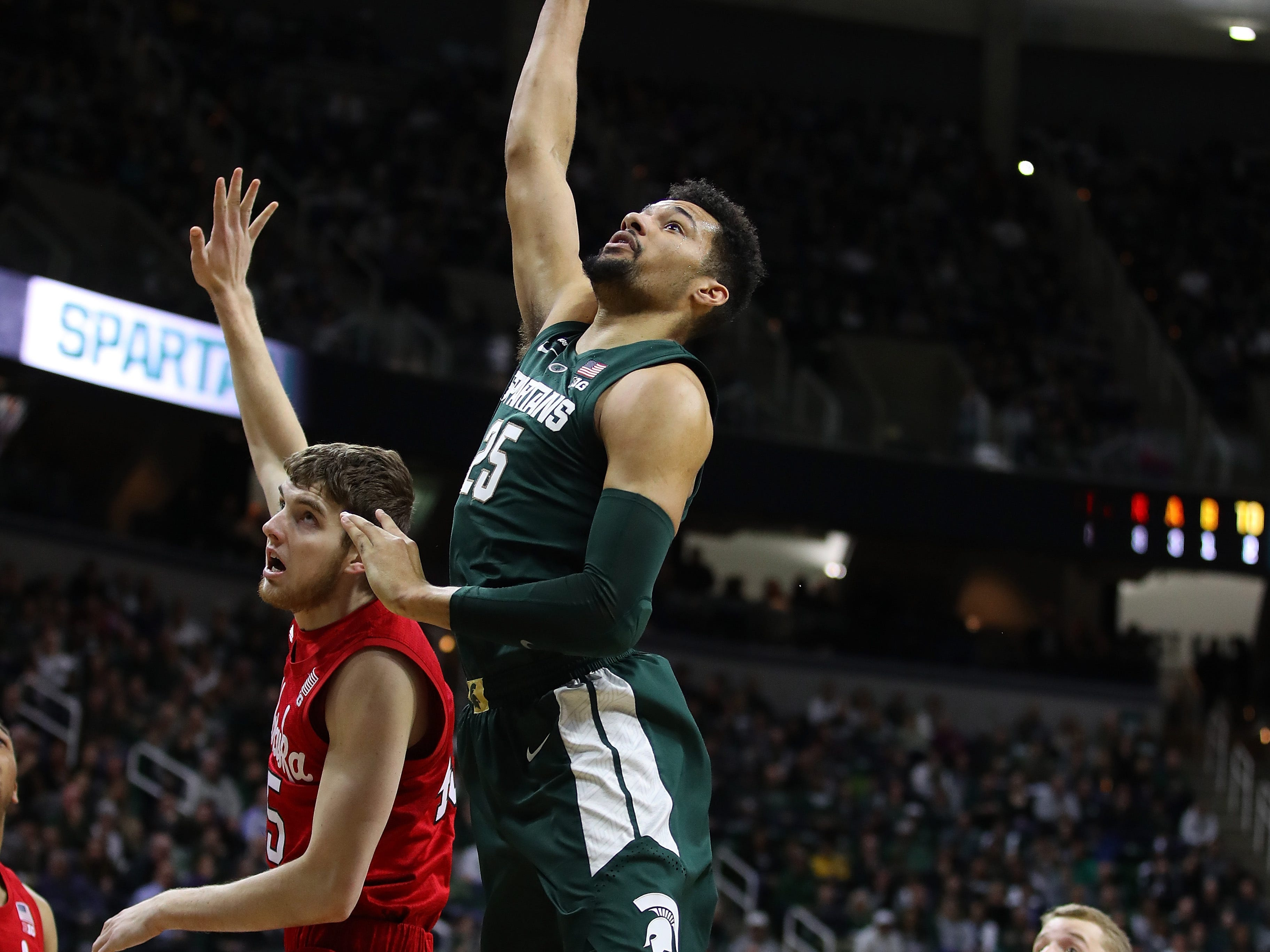 Kenny Goins (25) of the Michigan State Spartans takes a shot over Brady Heiman (45) of the Nebraska Cornhuskers during the first half at Breslin Center.