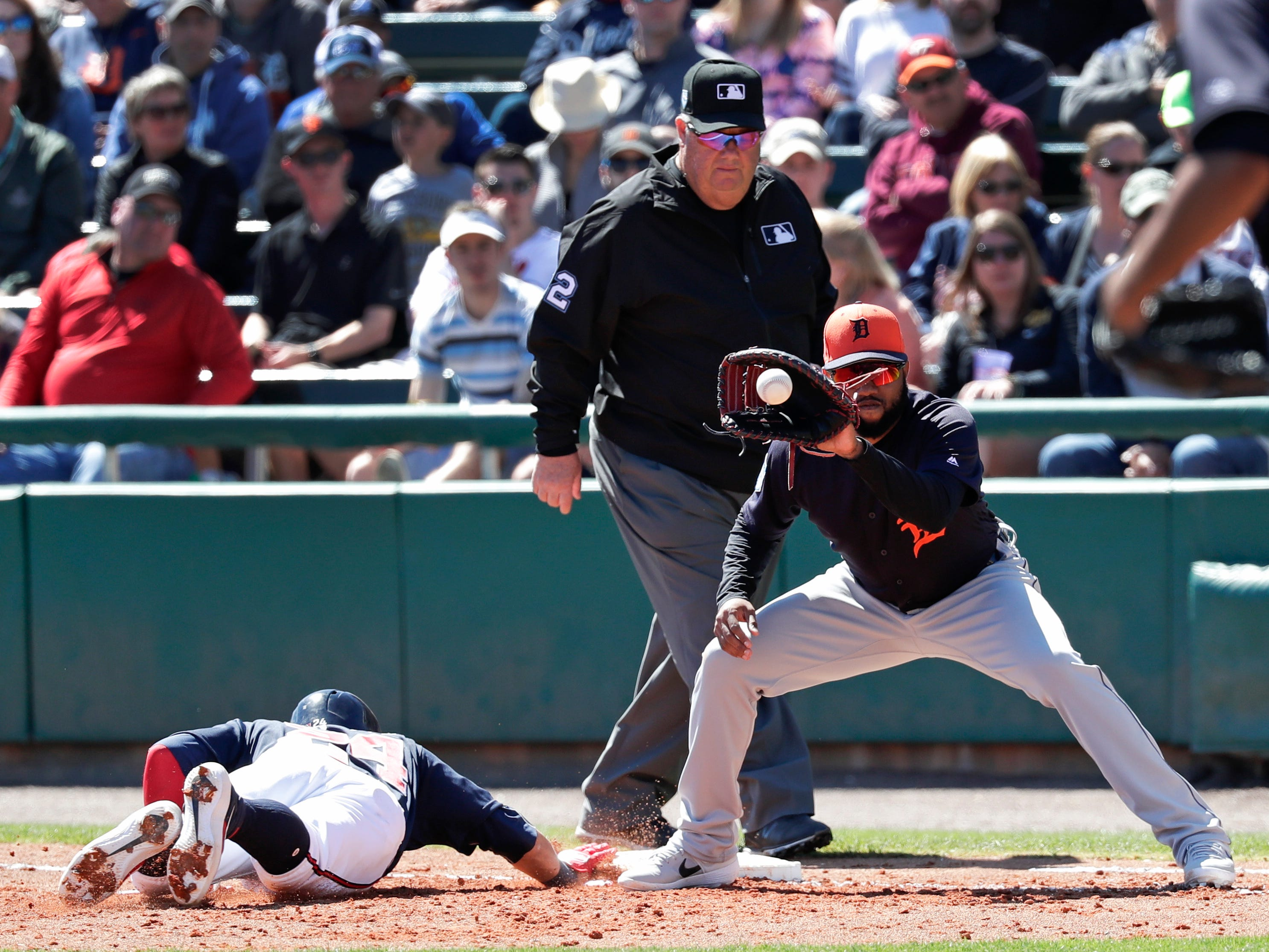 Atlanta Braves' Andres Blanco, left, dives back to first on a pick off attempt in the third inning as Detroit Tigers first baseman Ronny Rodriguez waits for the throw in a spring baseball exhibition game, Wednesday, March 6, 2019, in Kissimmee, Fla.