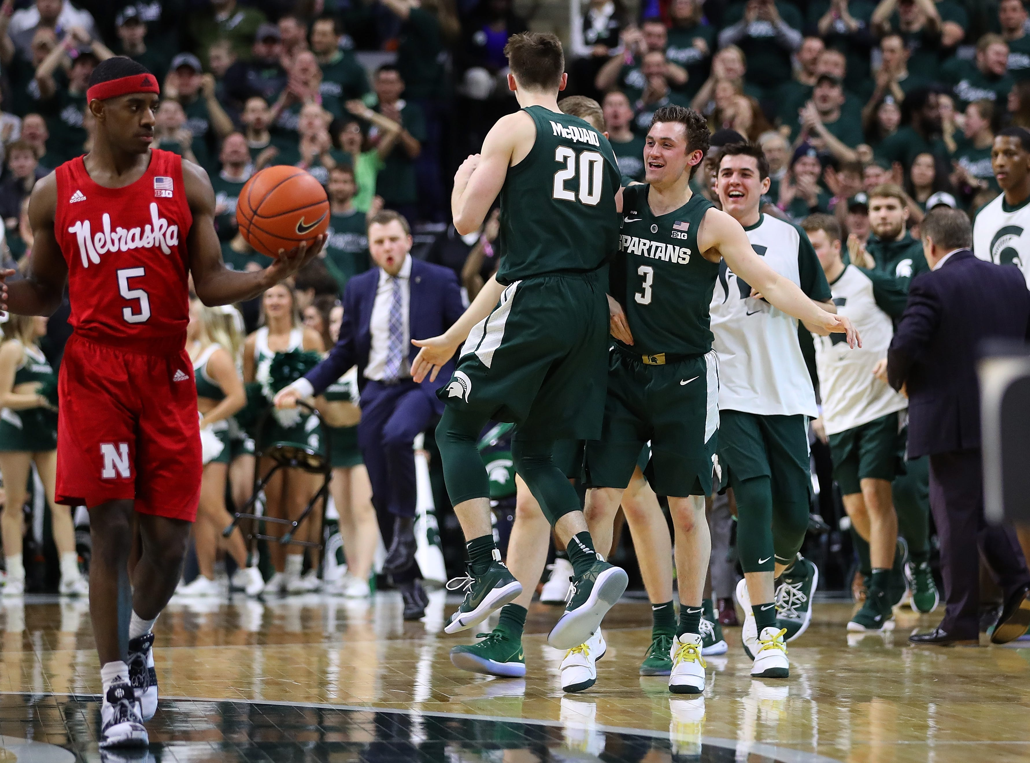 Matt McQuaid (20) of the Michigan State Spartans celebrates a second half three point basket with teammates behind Glynn Watson Jr. (5) of the Nebraska Cornhuskers at Breslin Center on March 05, 2019 in East Lansing, Michigan. Michigan State won the game 91-76.