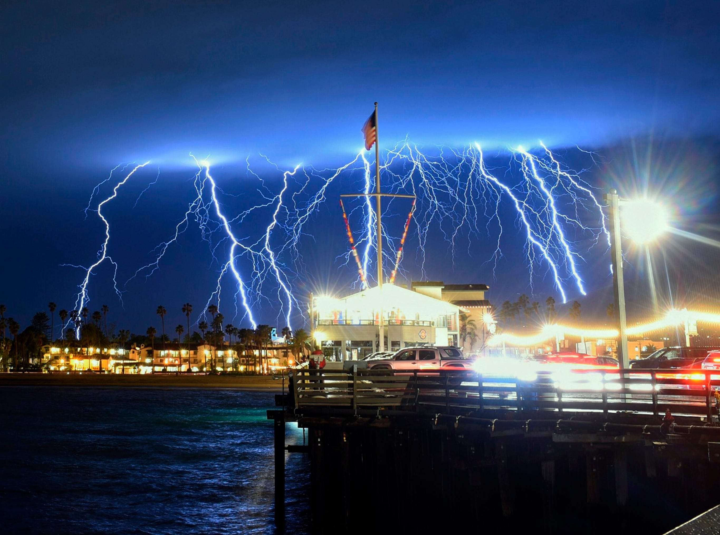 A time exposure photo shows a series of lightning strikes over Santa Barbara, Calif., seen from Stearns Wharf in the city's harbor, Tuesday evening, March 5, 2019. A storm soaking California on Wednesday could trigger mudslides in wildfire burn areas where thousands of residents are under evacuation orders, authorities warned.