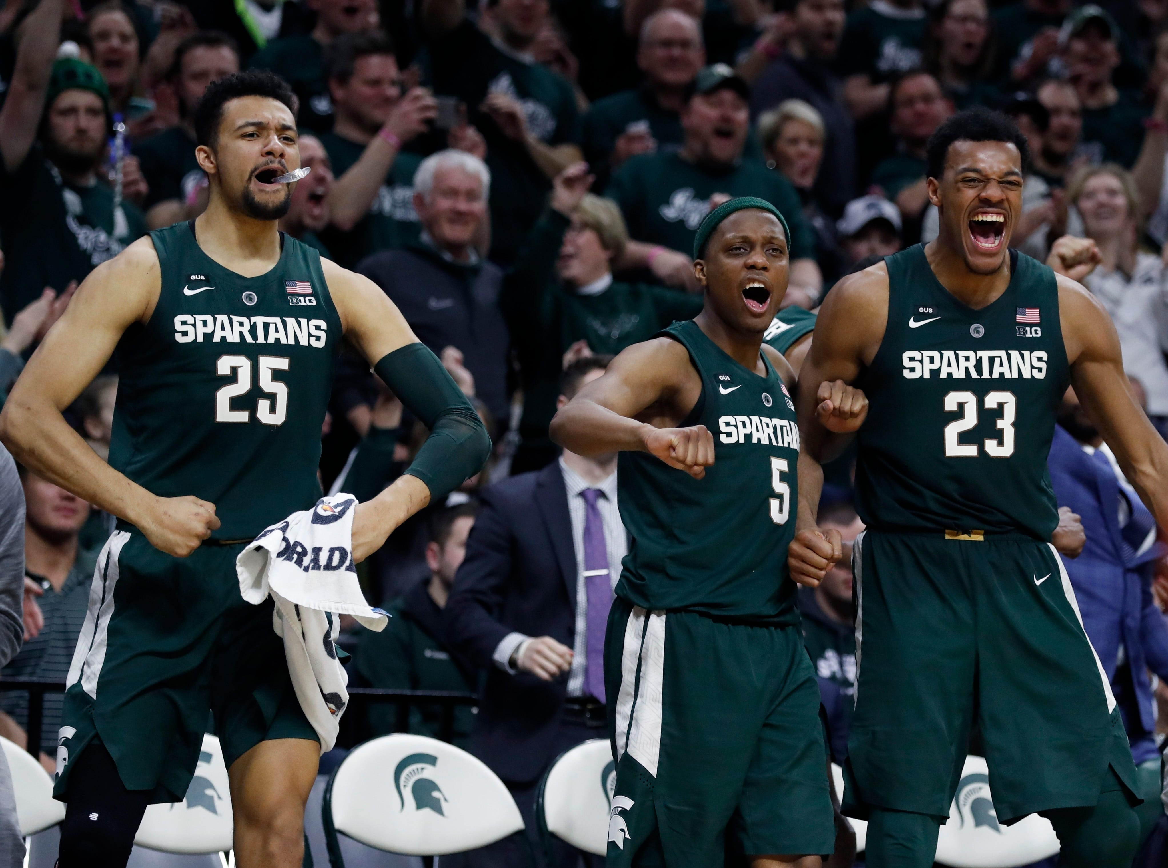 From left, Michigan State forward Kenny Goins (25), guard Cassius Winston (5), and forward Xavier Tillman (23) react after a basket by Brock Washington during the second half of an NCAA college basketball game against Nebraska, Tuesday, March 5, 2019, in East Lansing, Mich.