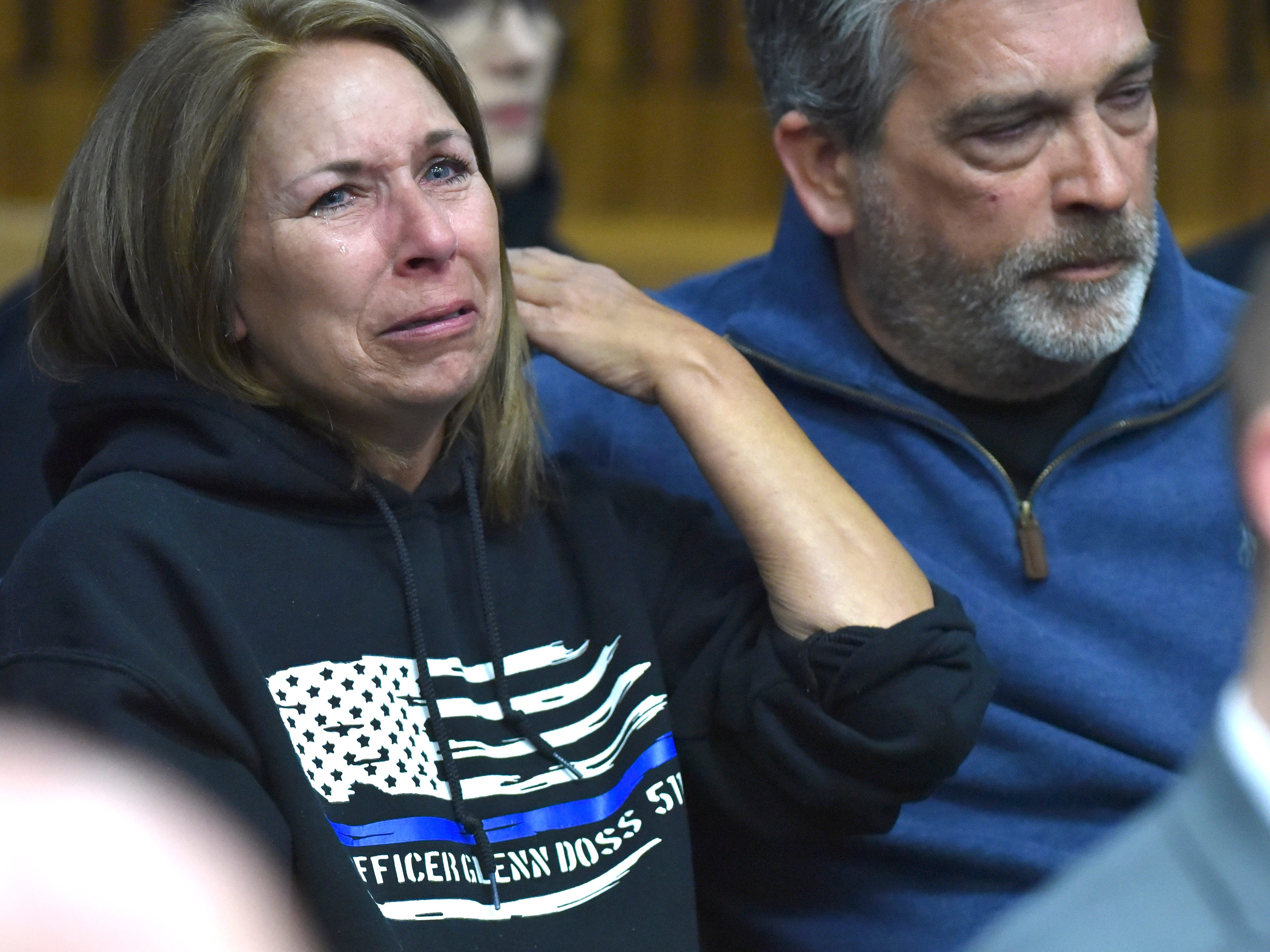 Michelle Crouse, left, wears a Thin Blue Line sweat shirt, memorializing Glenn Doss Jr., as she cries while sitting with her husband, Tim Crouse, as convicted murderer Decharlos Brooks apologizes to the Doss family. The Crouses' daughter  Emily was Doss Jr.'s fiancee.