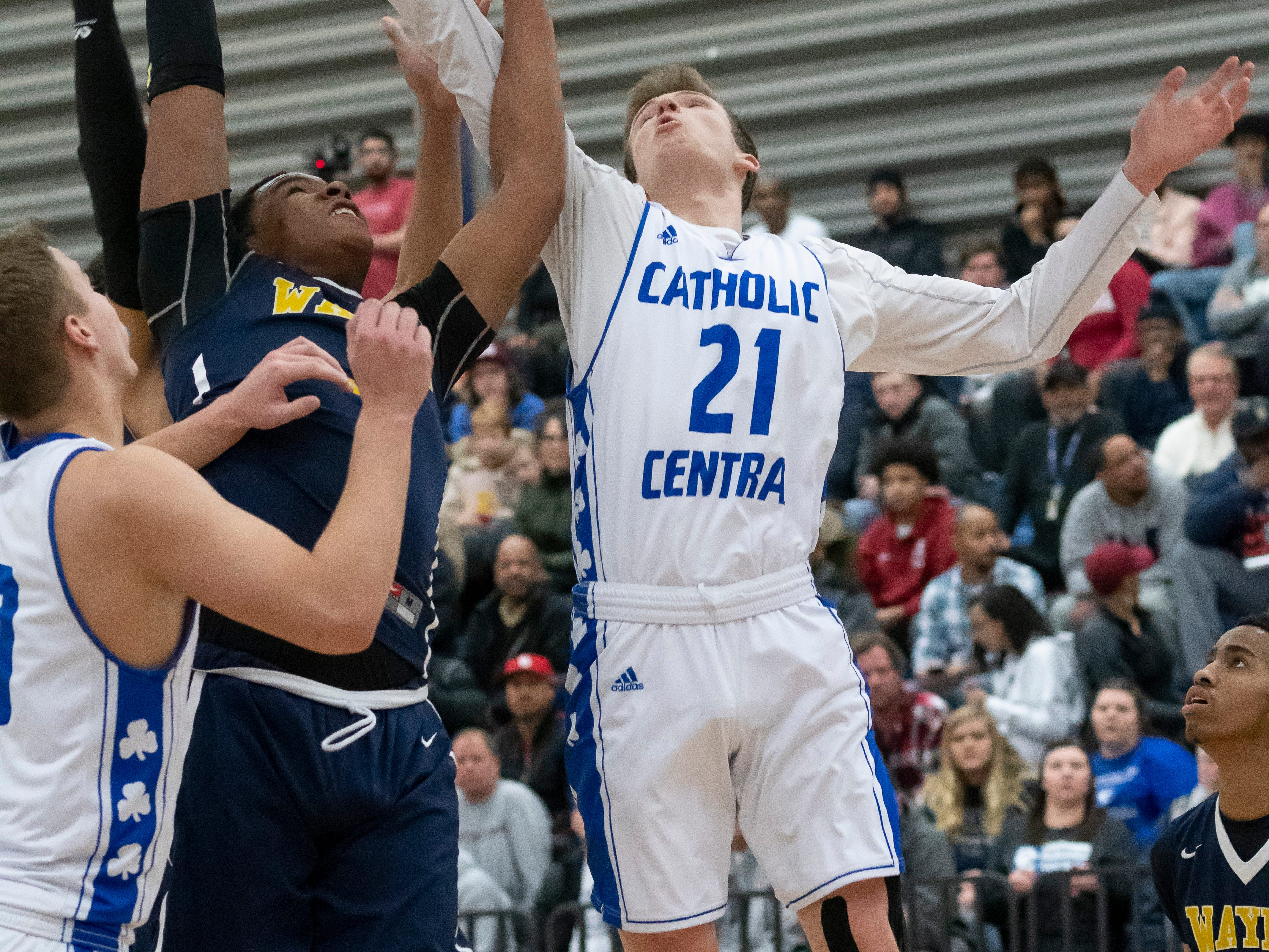 Wayne Memorial center Cartier Muse-Suber, left, and Detroit Catholic Central's Justin Rukat battle for a rebound in the first half.