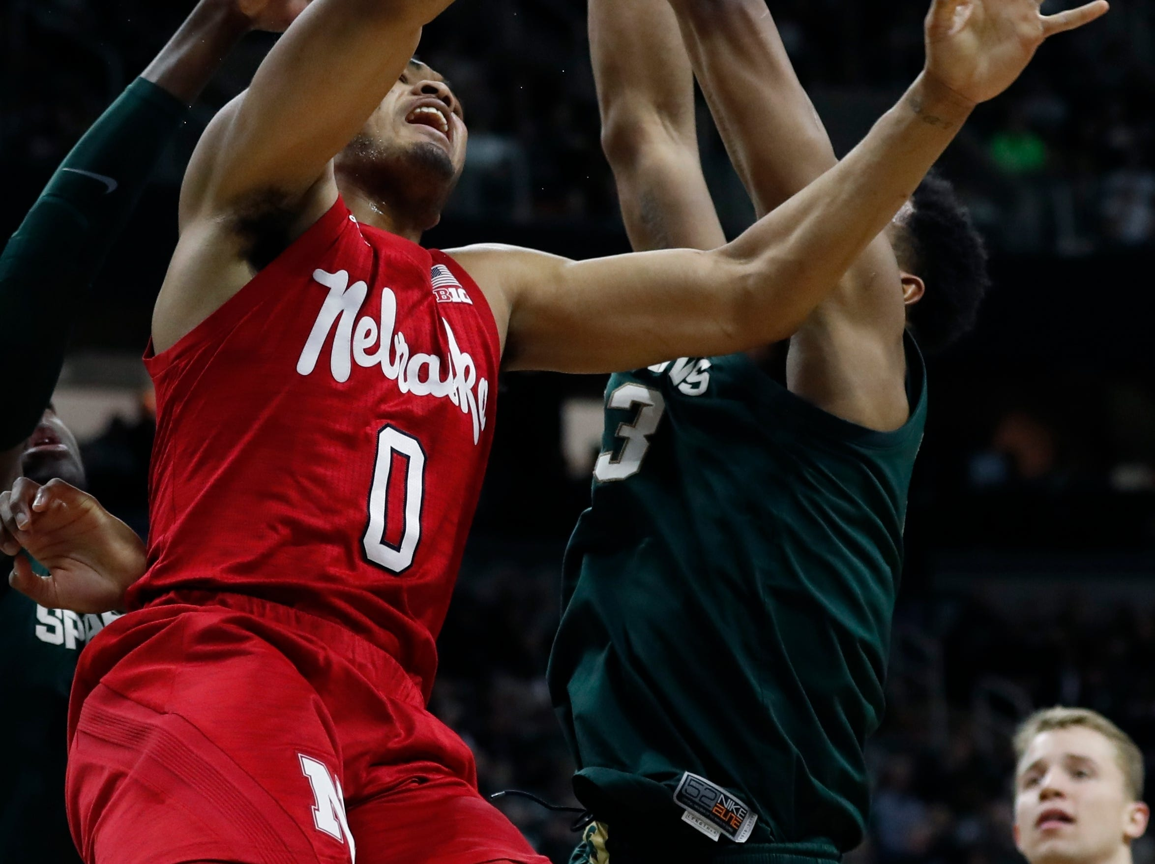 Nebraska guard James Palmer Jr. (0) loses control of the ball after running into Michigan State forwards Gabe Brown, left, and Xavier Tillman (23) during the first half of an NCAA college basketball game.
