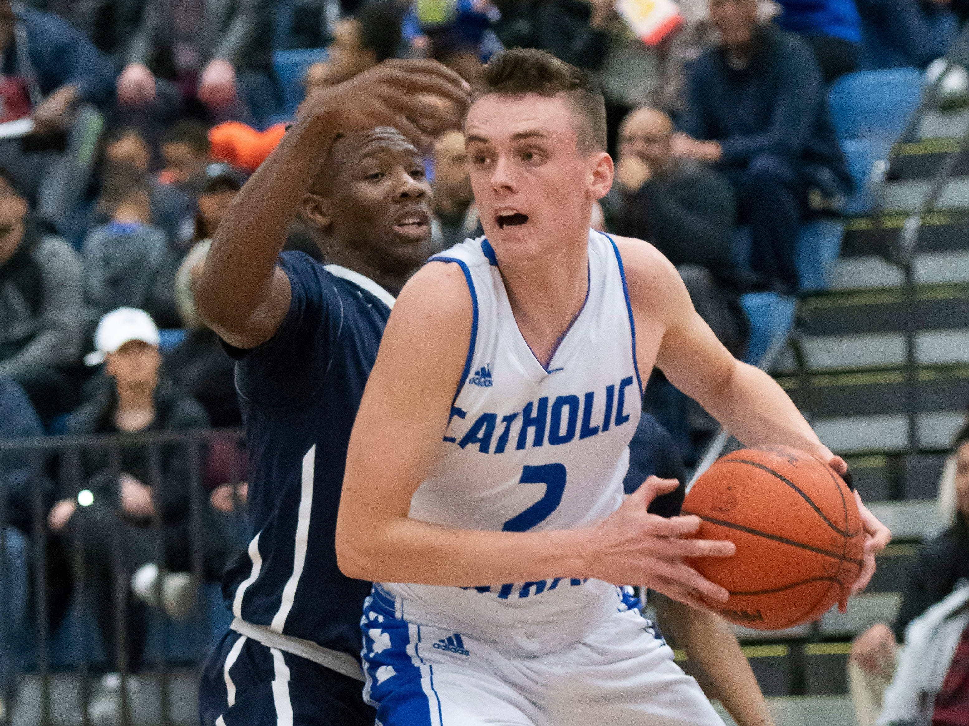 Detroit Catholic Central's Brendan Downs keeps the ball away from Wayne Memorial guard Chris Dobessi-Tindane in the first half.