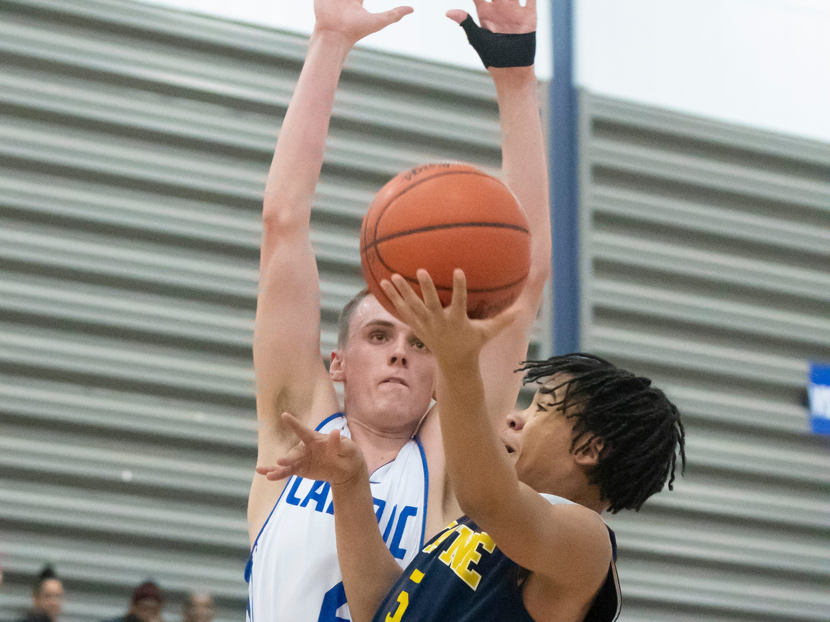 Detroit Catholic Central's Brendan Downs tries to stop a shot by Wayne Memorial guard Kenneth Bowie in the first half.