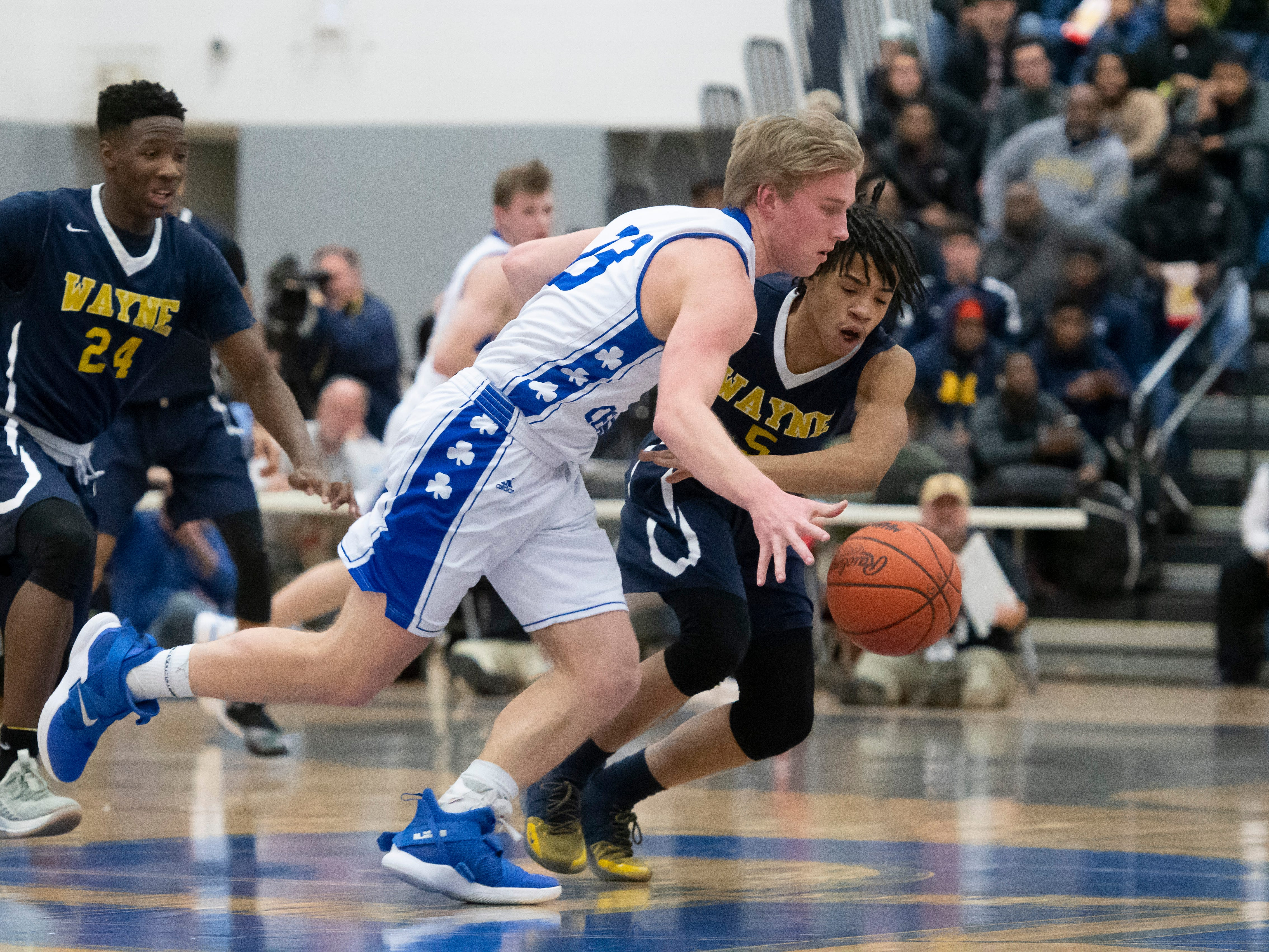 Detroit Catholic Central's Jacob Woebkenberg, left, tries to drive around Wayne Memorial guard Kenneth Bowie in the first half.