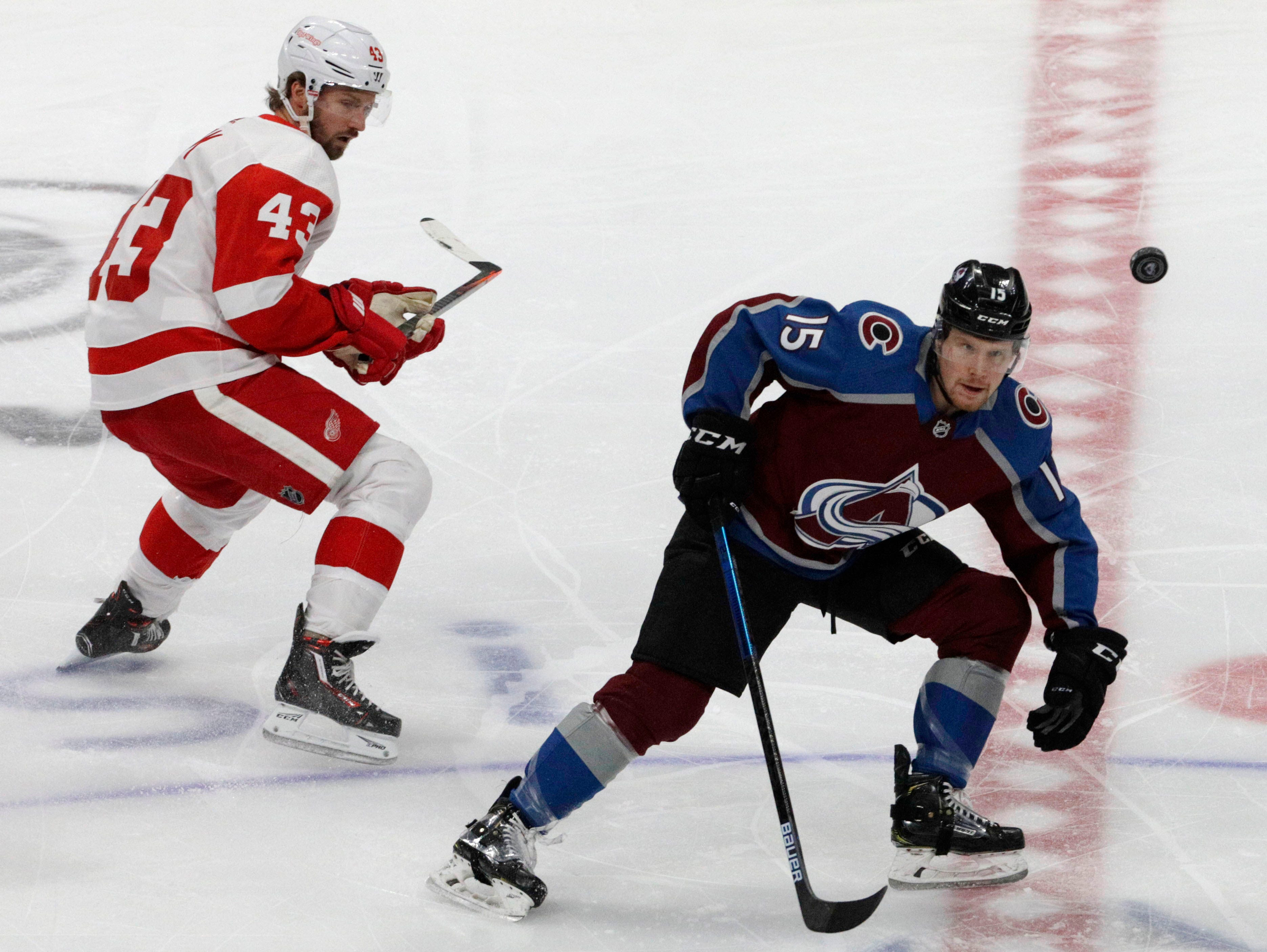 The puck passes by Colorado Avalanche center Sheldon Dries (15) and Detroit Red Wings left wing Darren Helm (43) during the first period of an NHL hockey game in Denver, Tuesday, March 5, 2019.