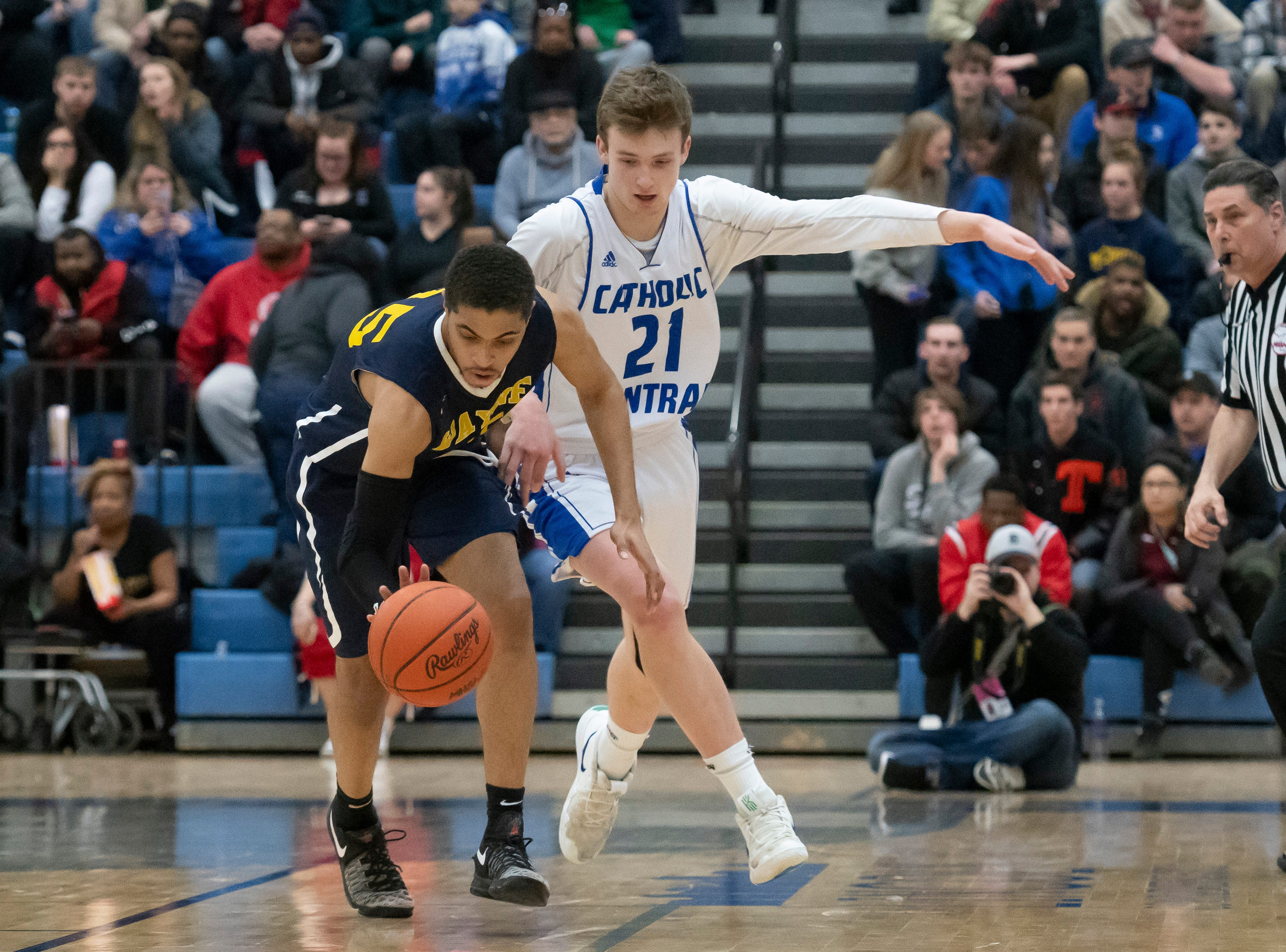 Wayne Memorial guard Chayce Leslie, left, and Detroit Catholic Central's Justin Rukat battle for a loose ball in the first half.