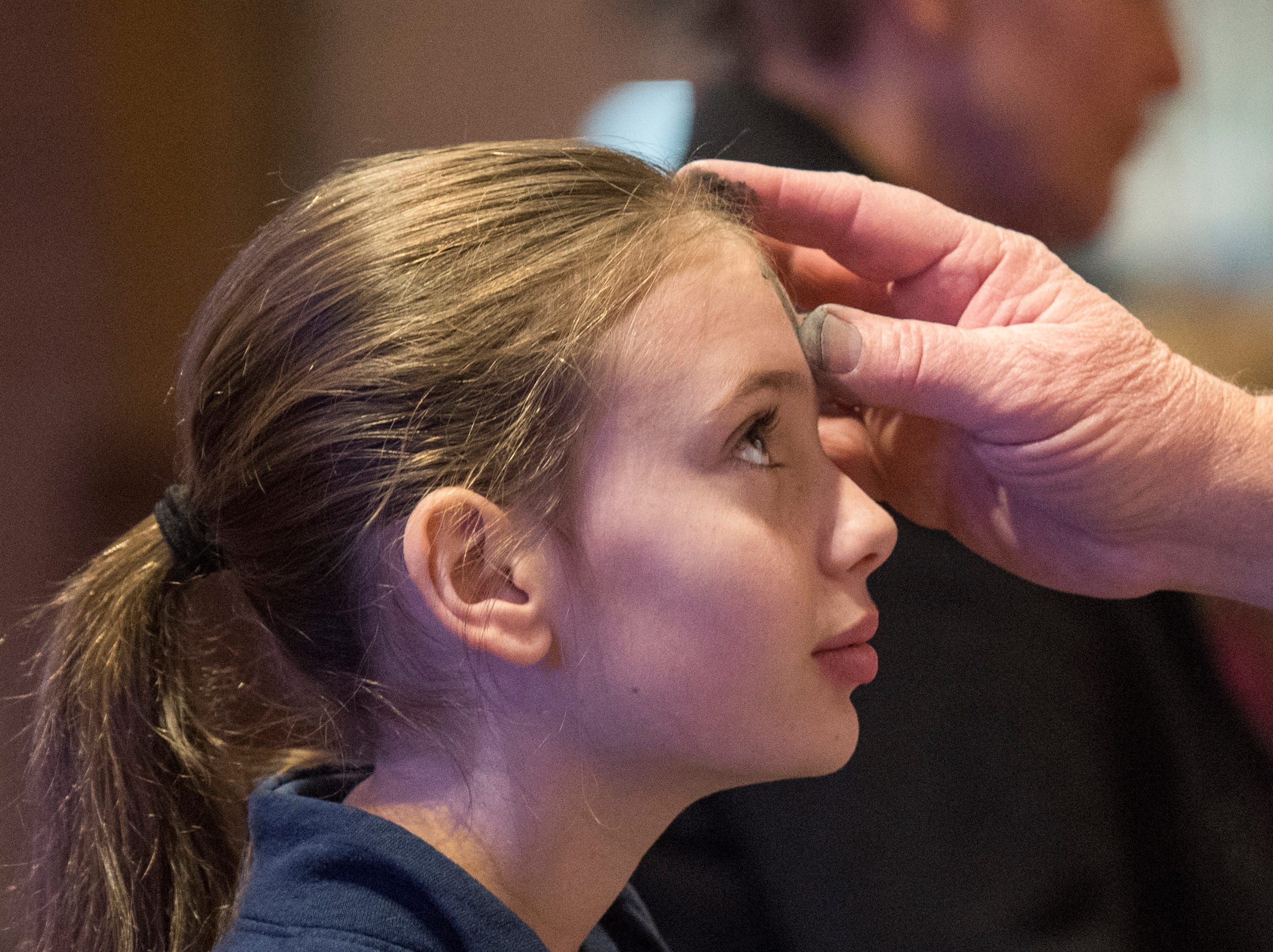 Corpus Christi fourth-grader Ruby Sammet receives ashes during Ash Wednesday Mass at Corpus Christi Church Wednesday, March 6, 2019.